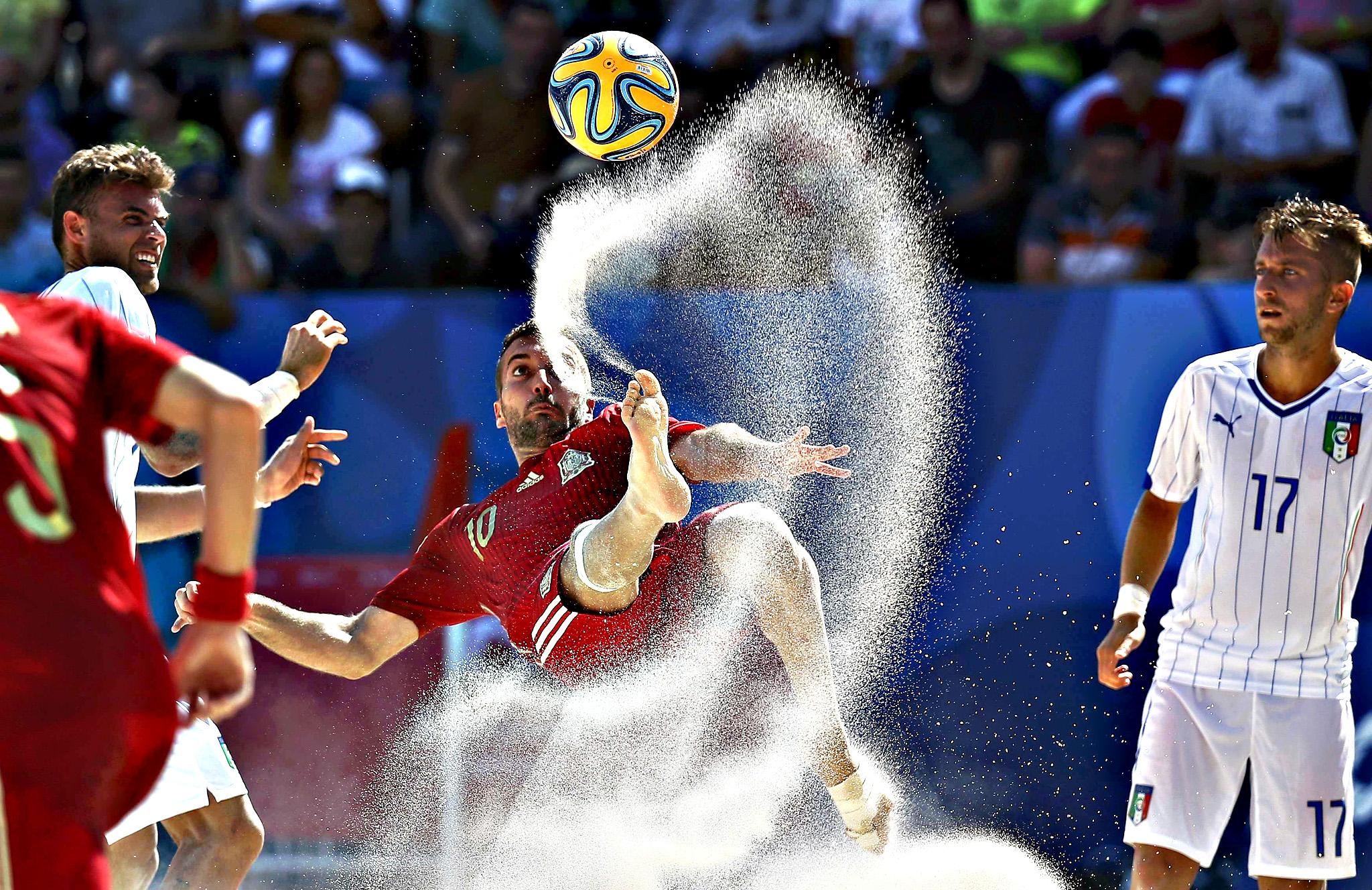 Llorenc Gomez of Spain kicks the ball next to Simone Marinai of Italy during their group stage beach football match at the 1st European Games in Baku, Azerbaijan, June 24, 2015.