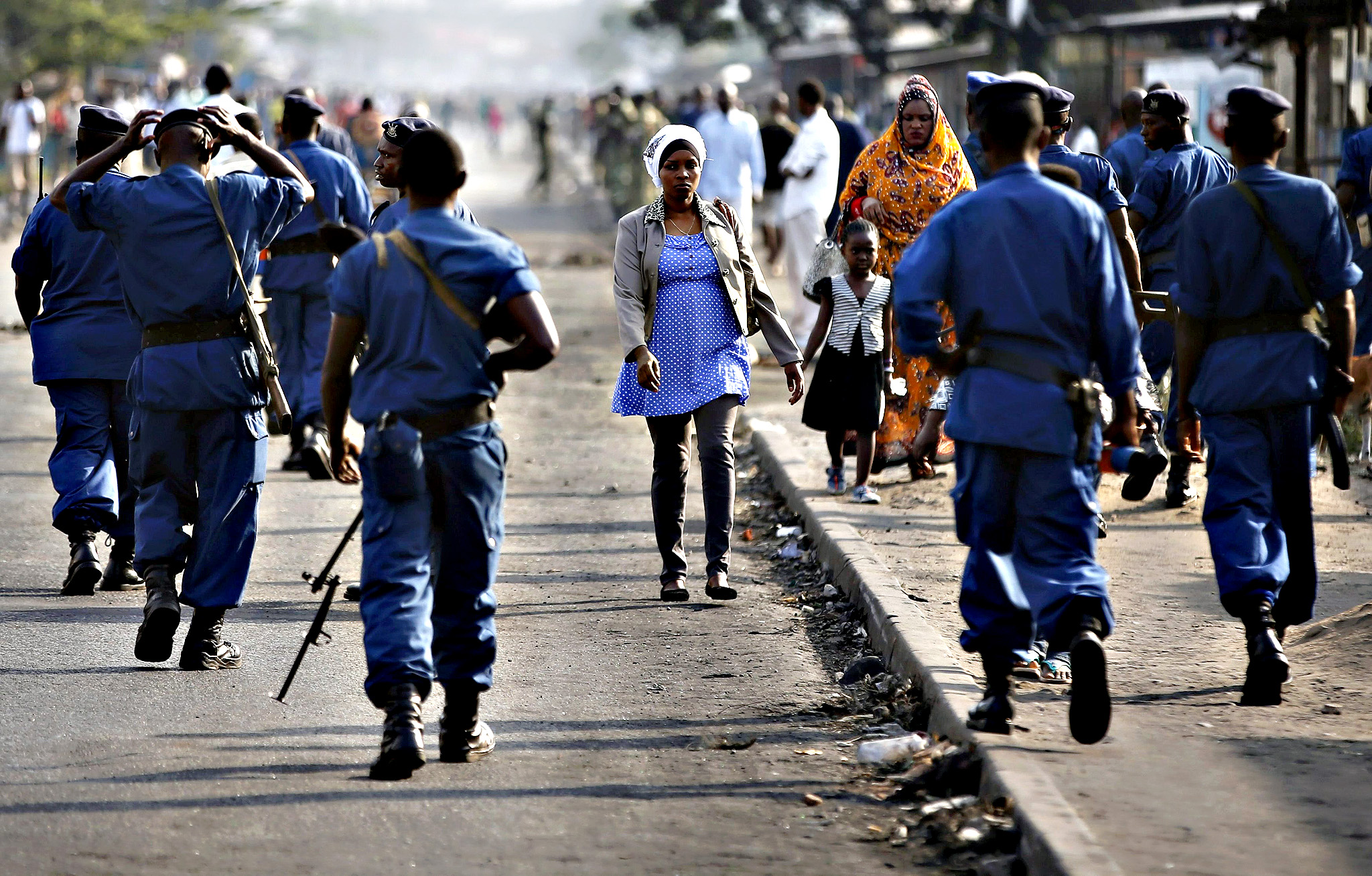 A woman passes by policemen during a protest against Burundi President Pierre Nkurunziza and his bid for a third term in Bujumbura, Burundi, June 2, 2015
