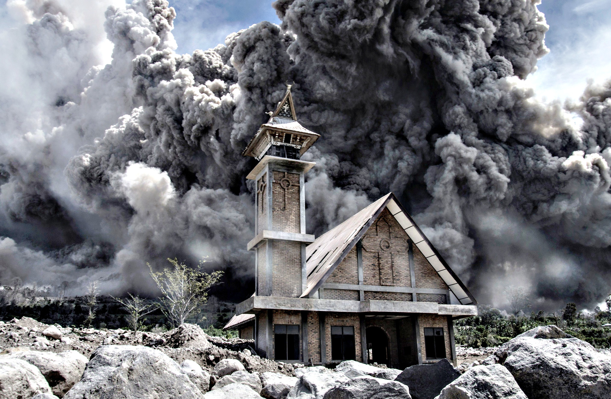 Ash from Mount Sinabung volcano fills the sky over an abandoned church during another eruption in Karo, in Indonesia's North Sumatra province on Friday. Sinabung rumbled back to life in 2013 after a period of inactivity, since when around 10,000 people have had to evacuate their homes