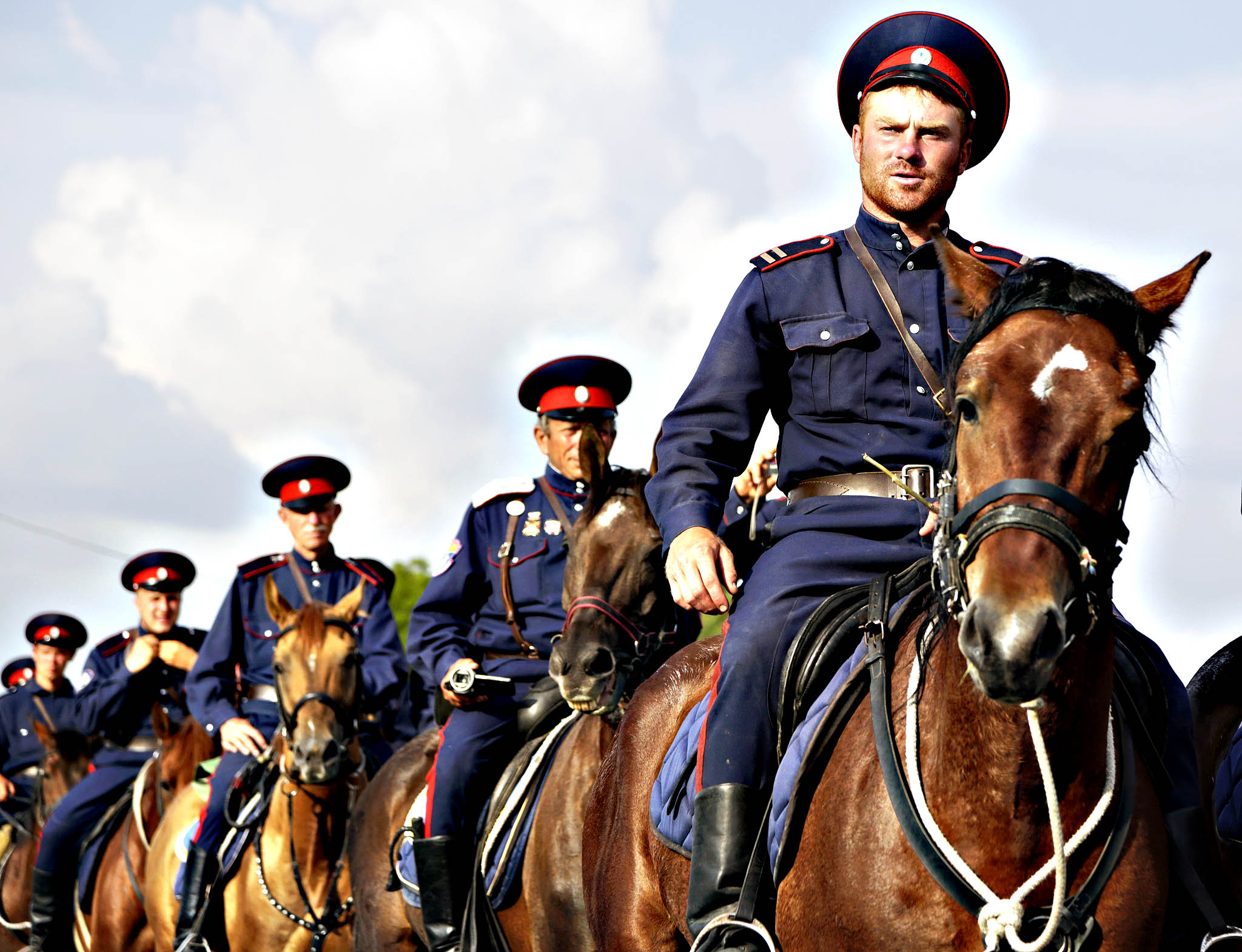 Mounted cossacks from the Southern Russian city of Volgograd wear period uniforms as they ride along a street during a demonstration of patriotism in Simferopol on June 5, 2015.