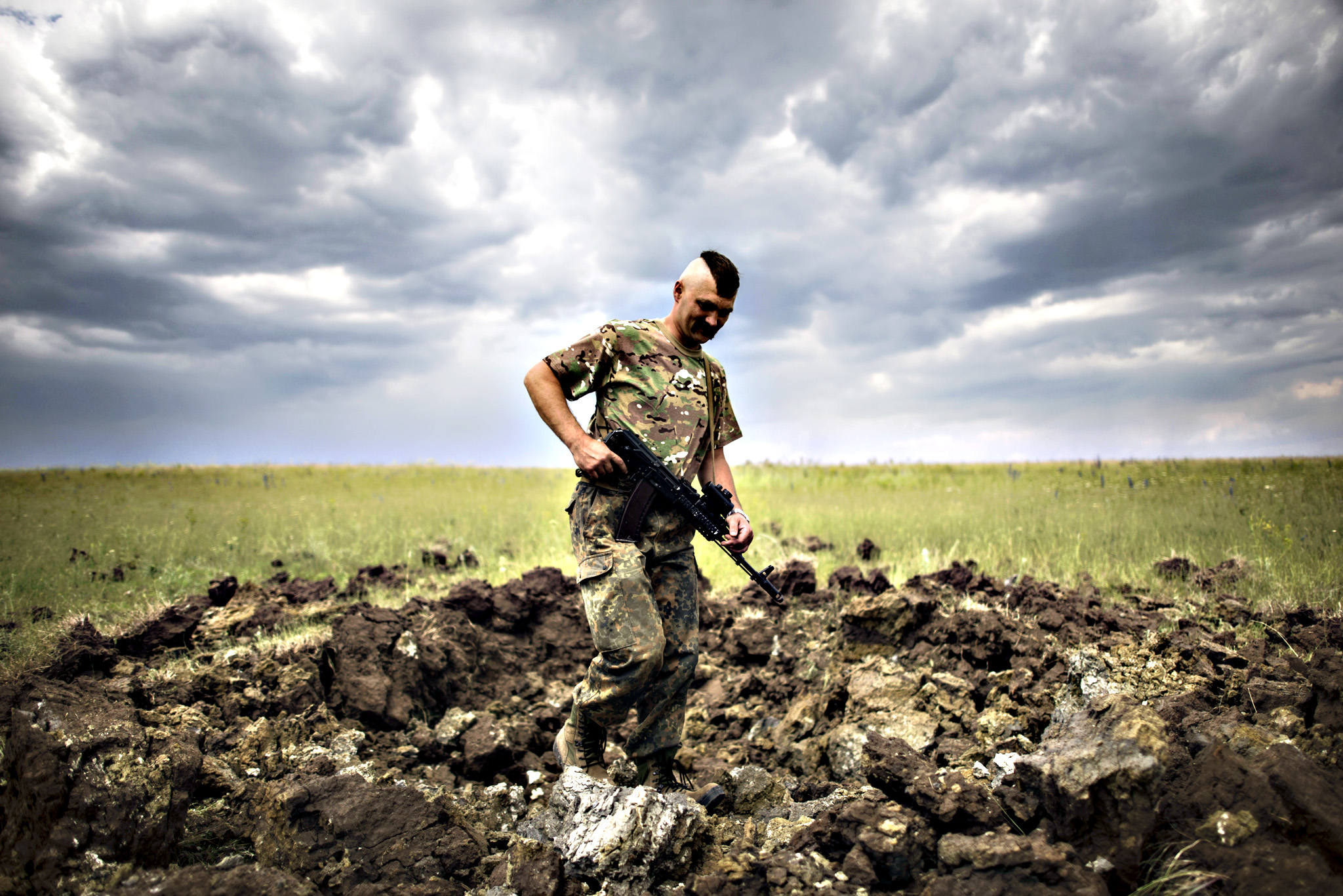A Ukrainian serviceman investigates a crater left by a Grad rocket in the village of Toshkivka, Luhansk region, eastern Ukraine, Monday, June 15, 2015