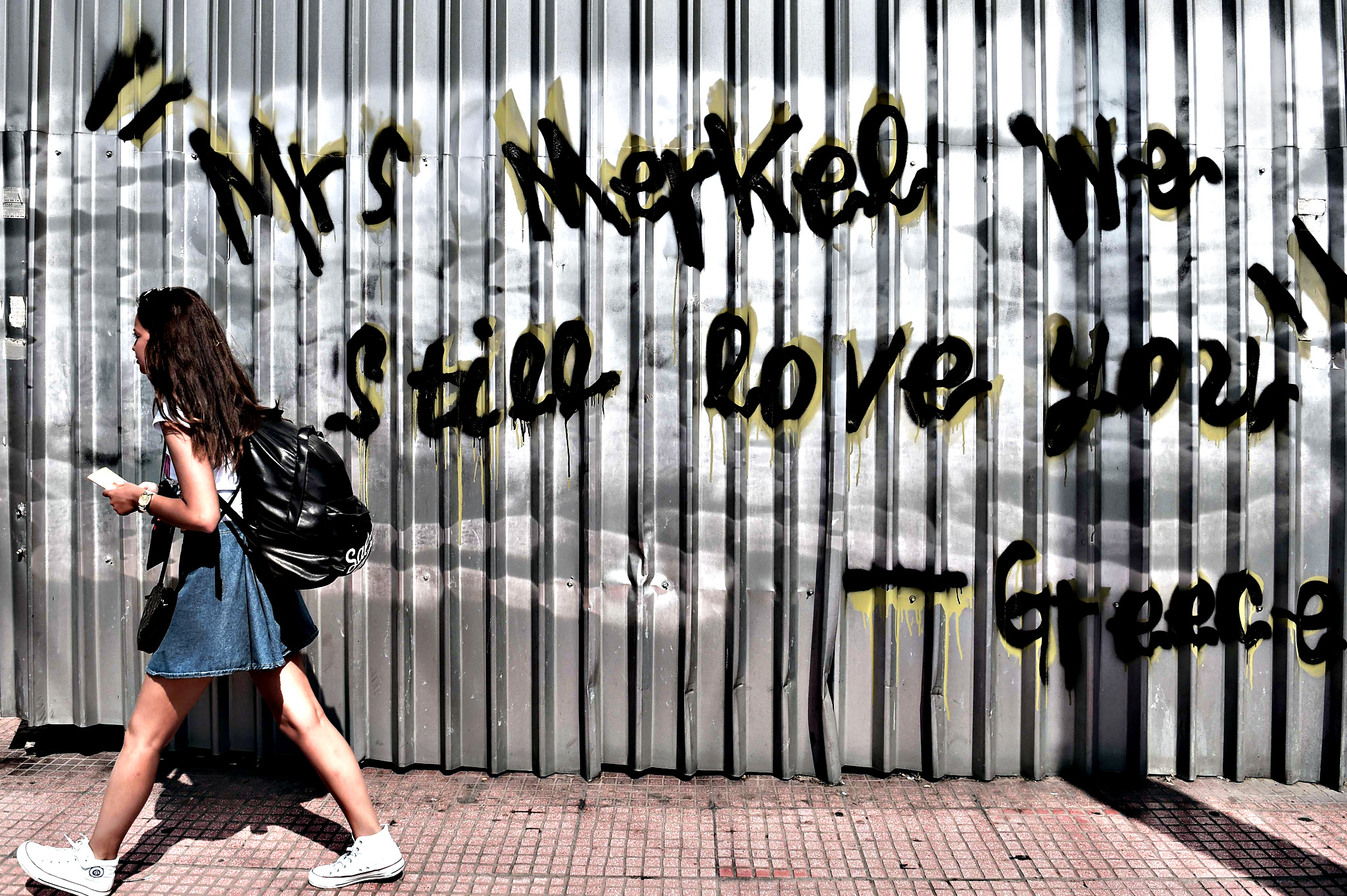 "A young woman walks past a graffiti reading ""Mrs Merkel we still love you - Greece"" in central Athens on June 19, 2015. The European Central Bank's decision-making governing council will hold an emergency session on June 19 to discuss a request from the Bank of Greece for an increase in liquidity to Greek banks"