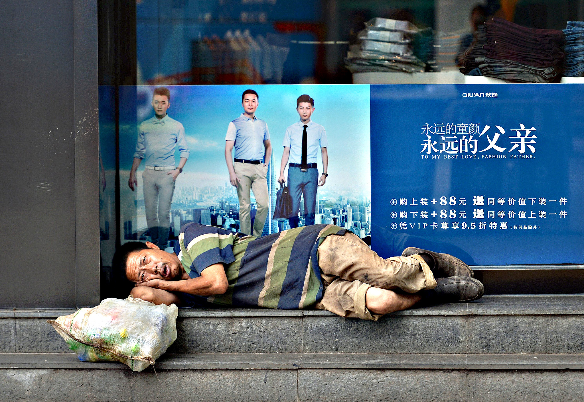 A garbage collector rests in front of a clothing store with an advertisement on the glass window in Hefei, Anhui province, China, June 9, 2015