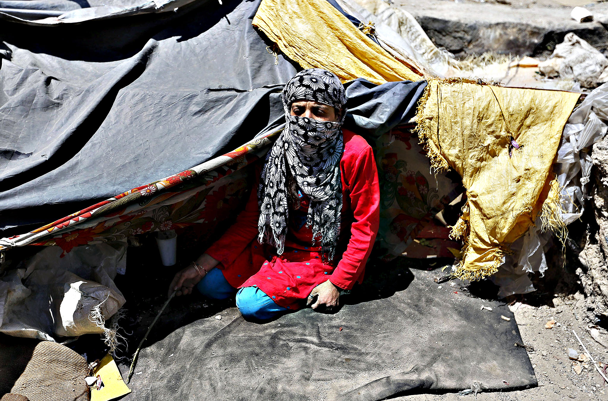 .A female Afghan drug addict sits near a bridge inhabited by drug addicts in Kabul, Afghanistan June 1, 2015