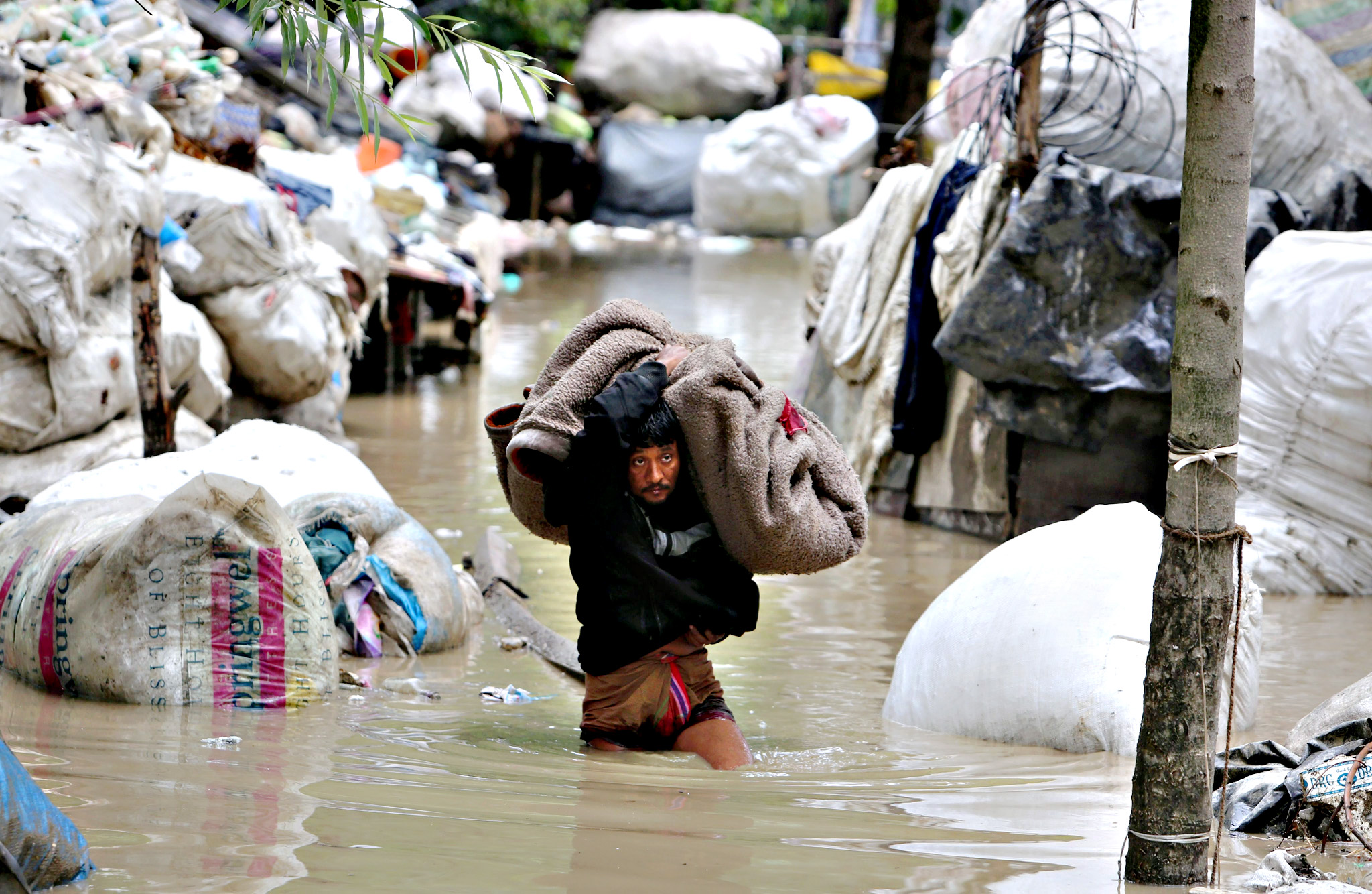 An Indian rag picker carrying goods wades a water logged area after breach in River Jheluml in Srinagar, summer capital of Indian Kashmir, 25 June 2015. A flood alert was sounded in Jammu and Kashmir state on 25 June after the Jhelum and other rivers rose beyond their danger levels.