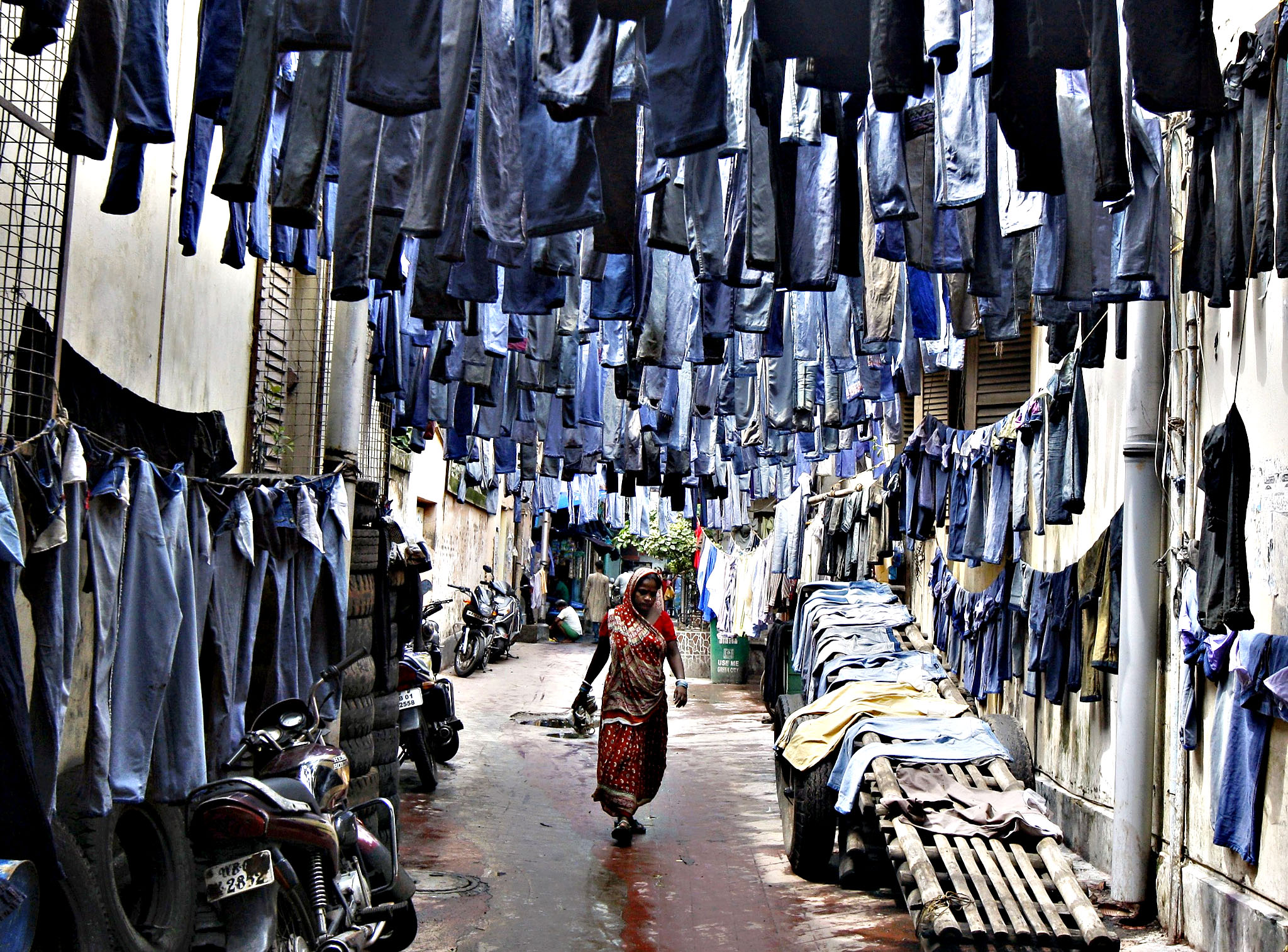 A woman walks through an alley as used pairs of jeans are hung to dry before they are sold in a second-hand clothes market in Kolkata, India, June 29, 2015