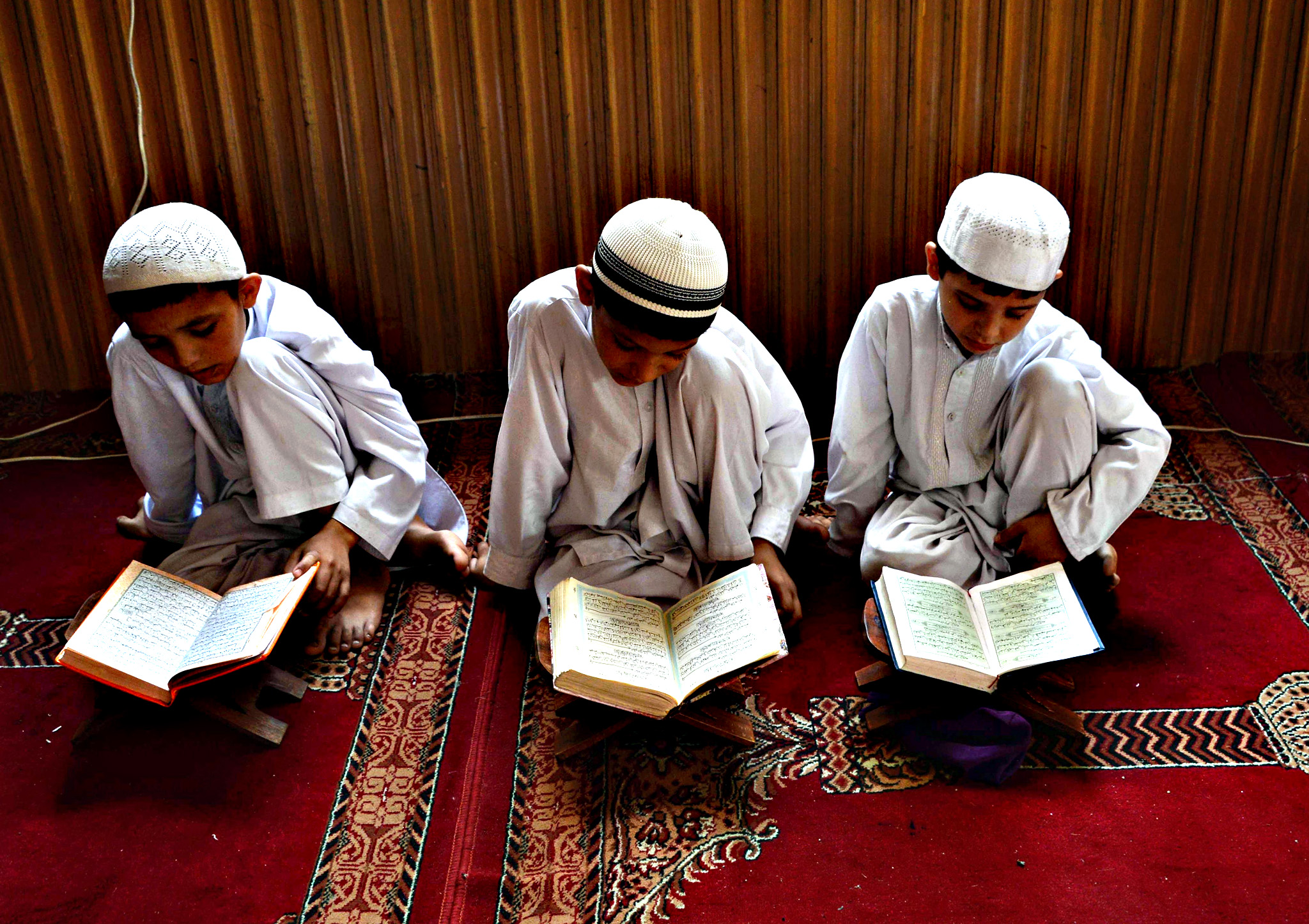 Afghan children study the Koran during first day of the month of Ramadan at a mosque in Jalalabad on Thursday, Islam's holy month of Ramadan, which is calculated on the sighting of the new moon, will begin on June 18 in Afghanistan. Muslims all over the world fast from dawn until dusk and dates are usually eaten to break the fast