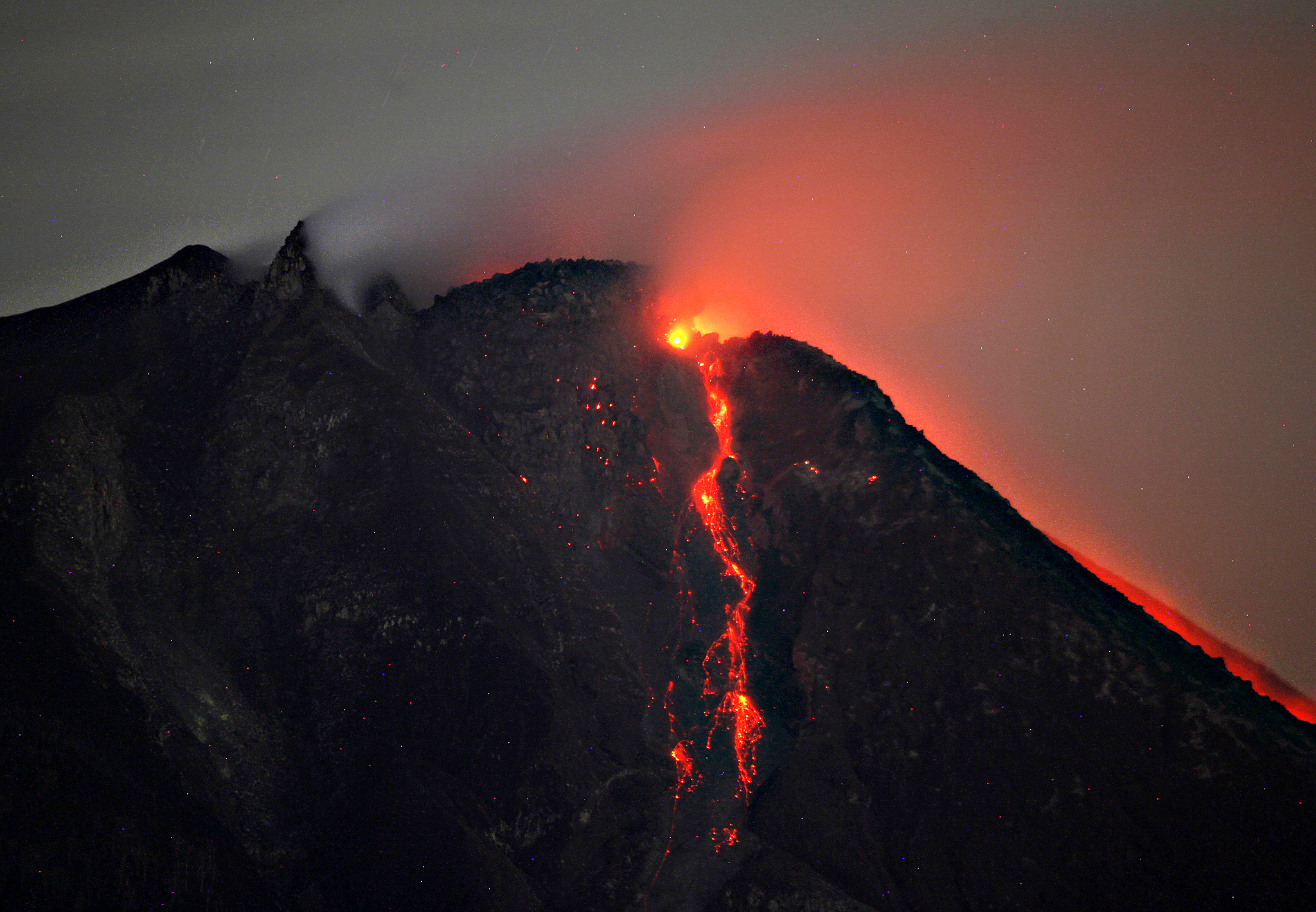 Hot lava flows from the crater of Mount Sinabung as seen from Tiga Pancur, North Sumatra, Indonesia, early Thursday. Mount Sinabung, one of about 130 active volcanoes in the country, has been put at the highest alert level since June 2 due to the growing size of its lava dome.