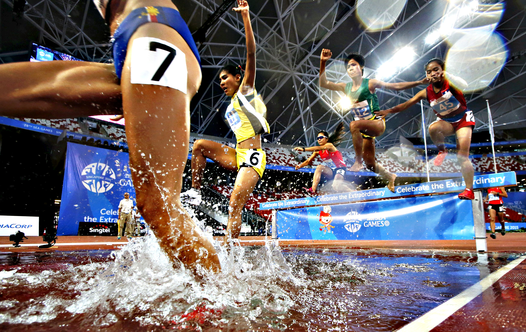 Contestants jump into the water pit during the women's 3000m steeplechase finals at the Southeast Asian (SEA) Games in Singapore June 12, 2015.