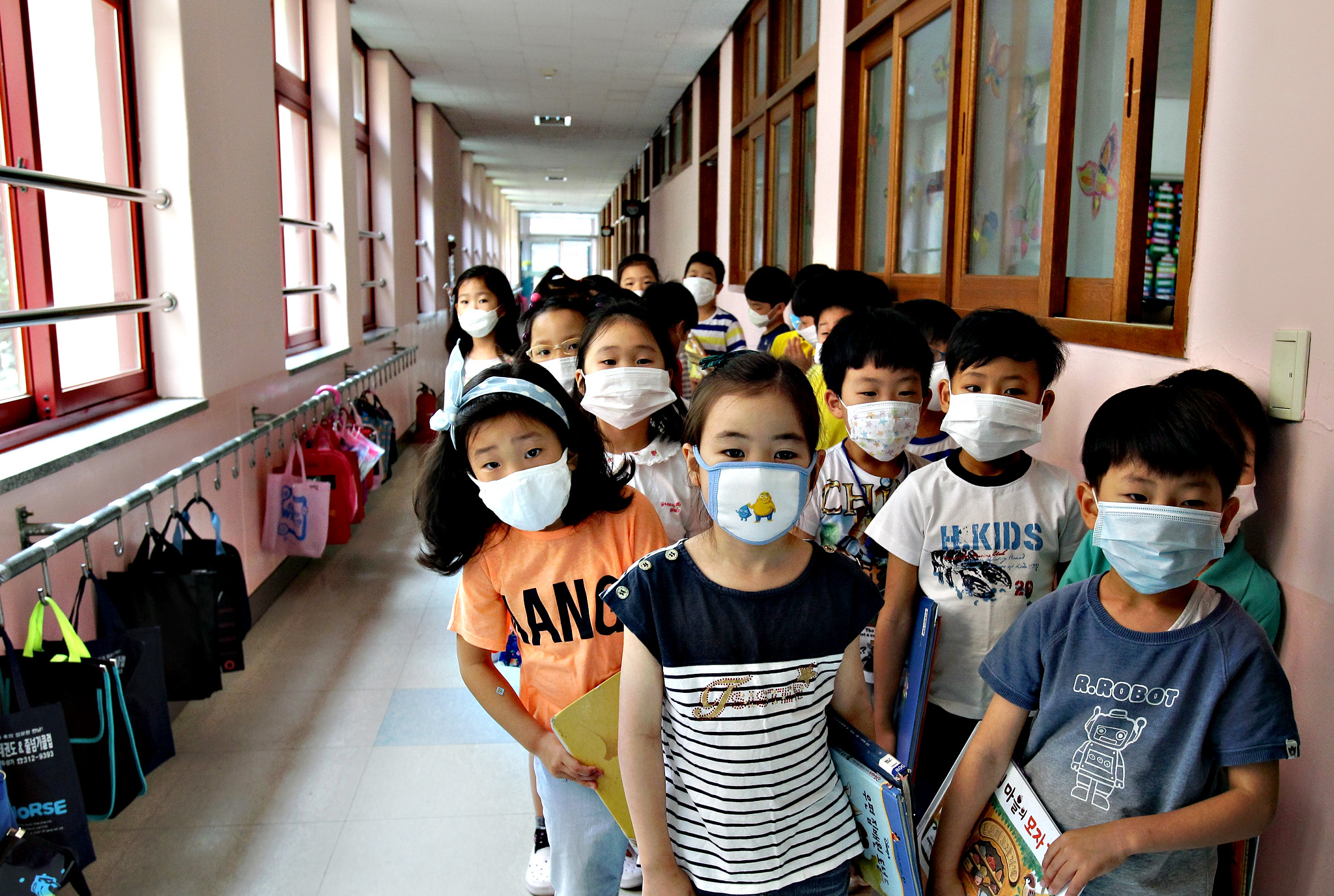 Elementary school students wear masks as a precaution against the MERS virus as they wait for a lesson to start at Midong Elementary School on June 9, 2015 in Seoul, South Korea. South Korea has reported eight deaths related to the virus with 2,500 people quarantined and 1,800 schools closed as of June 9, 2015