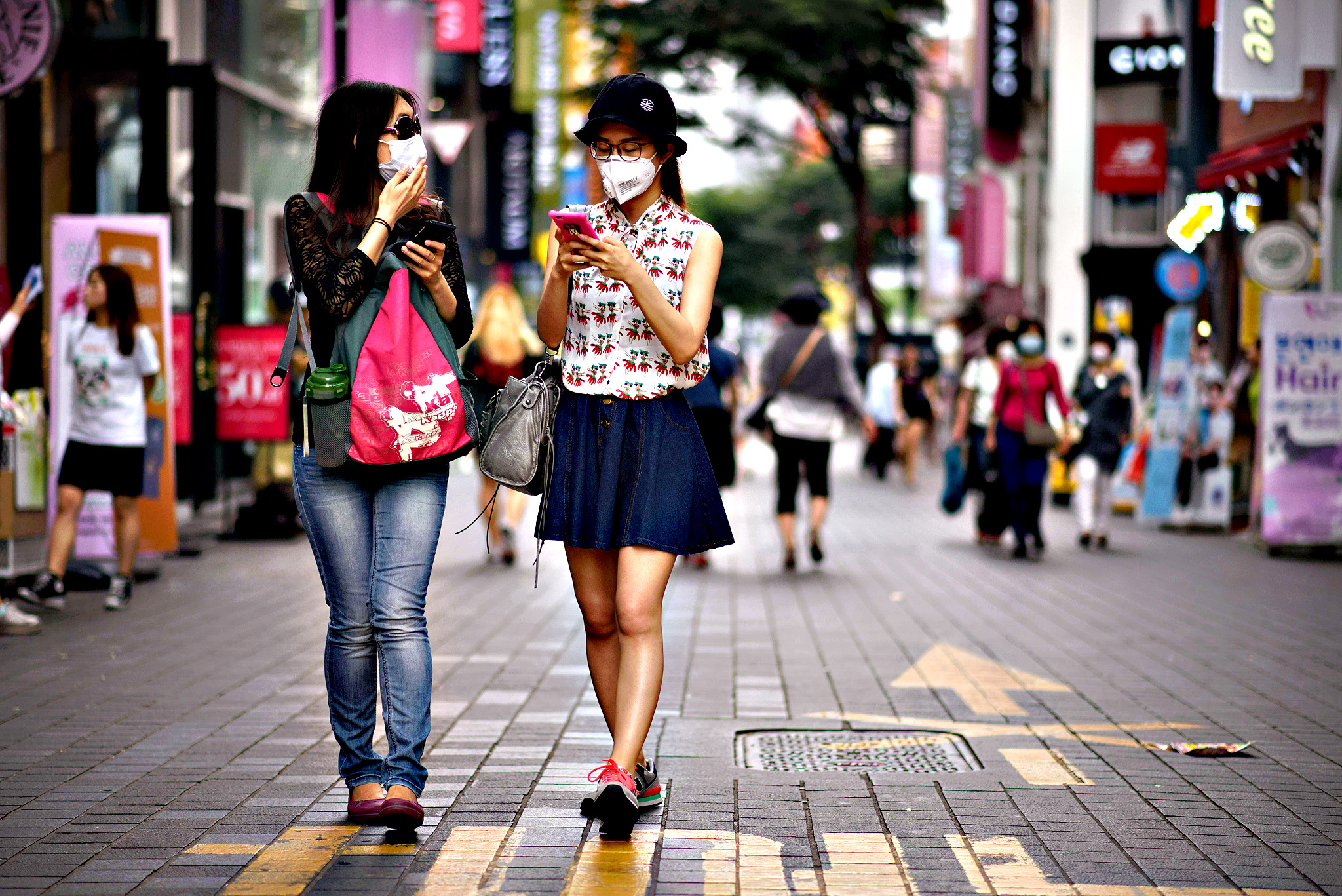 Two women wearing face masks walk on a street in the popular Myeongdong shopping district in Seoul on June 15, 2015. South Korea reported on June 15, two more deaths and five new cases in the growing outbreak of MERS which has placed more than 5,200 people under quarantine and sparked widespread
