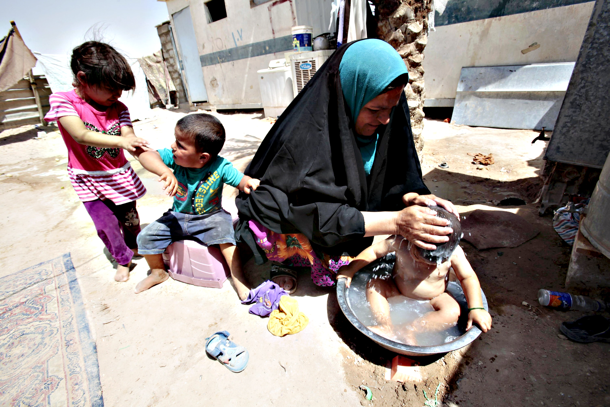 A displaced Sunni woman, fleeing violence from Mosul washes her child on the outskirts of Najaf, south of Baghdad June 24, 2015