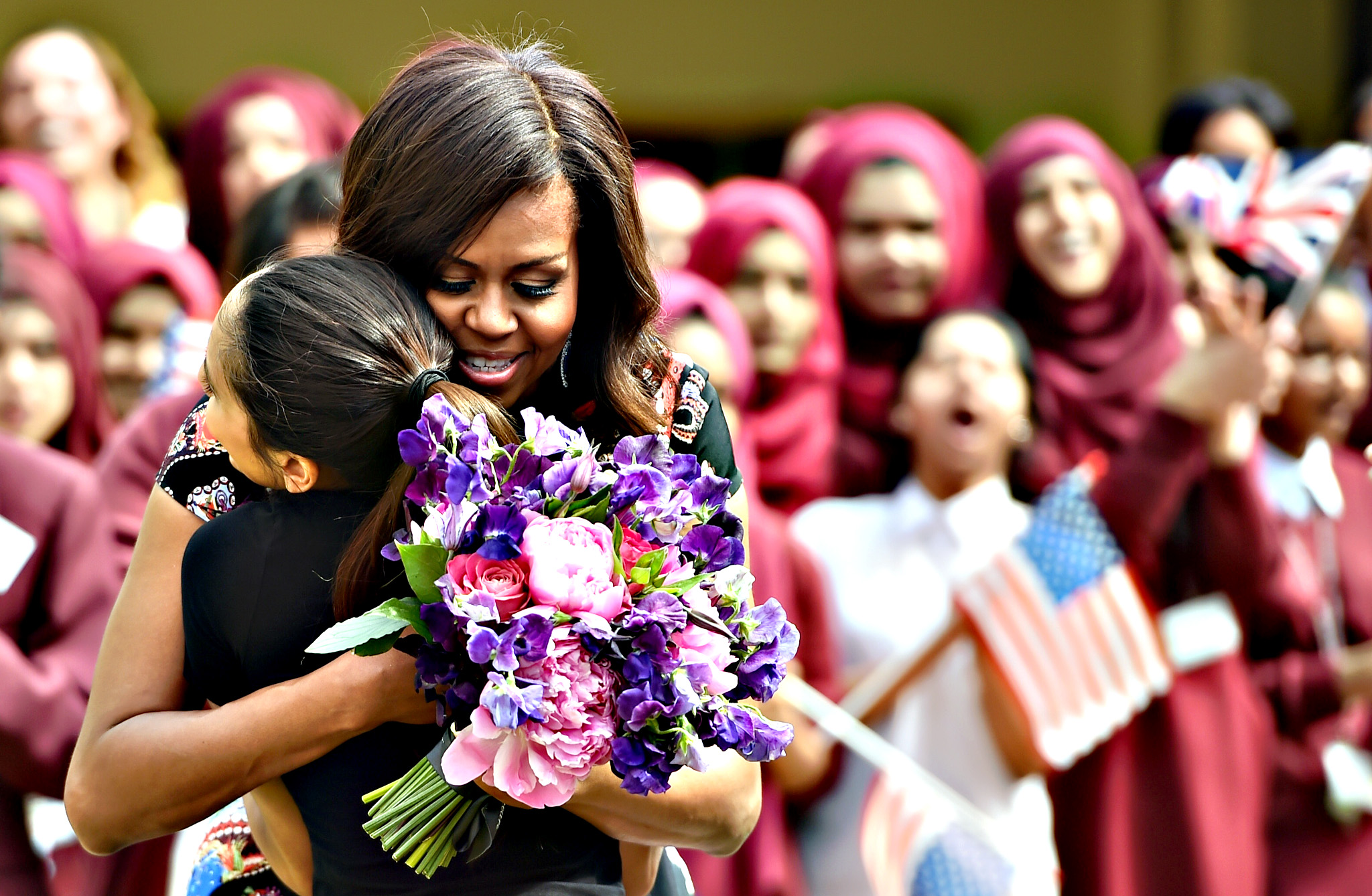 A student gives flowers to, embraces and welcomes with other young students US First Lady Michelle Obama in the courtyard before an event as part of the 'Let Girls Learn Initiative' at the Mulberry School for Girls on Tuesday in London, England. The US First Lady is travelling with her daughters, Malia and Sasha and her mother, Mrs. Marian Robinson, to continue a global tour promoting her 'Let Girls Learn Initiative'. The event at the school was to discuss how the UK and USA are working together to expand girl's education around the world