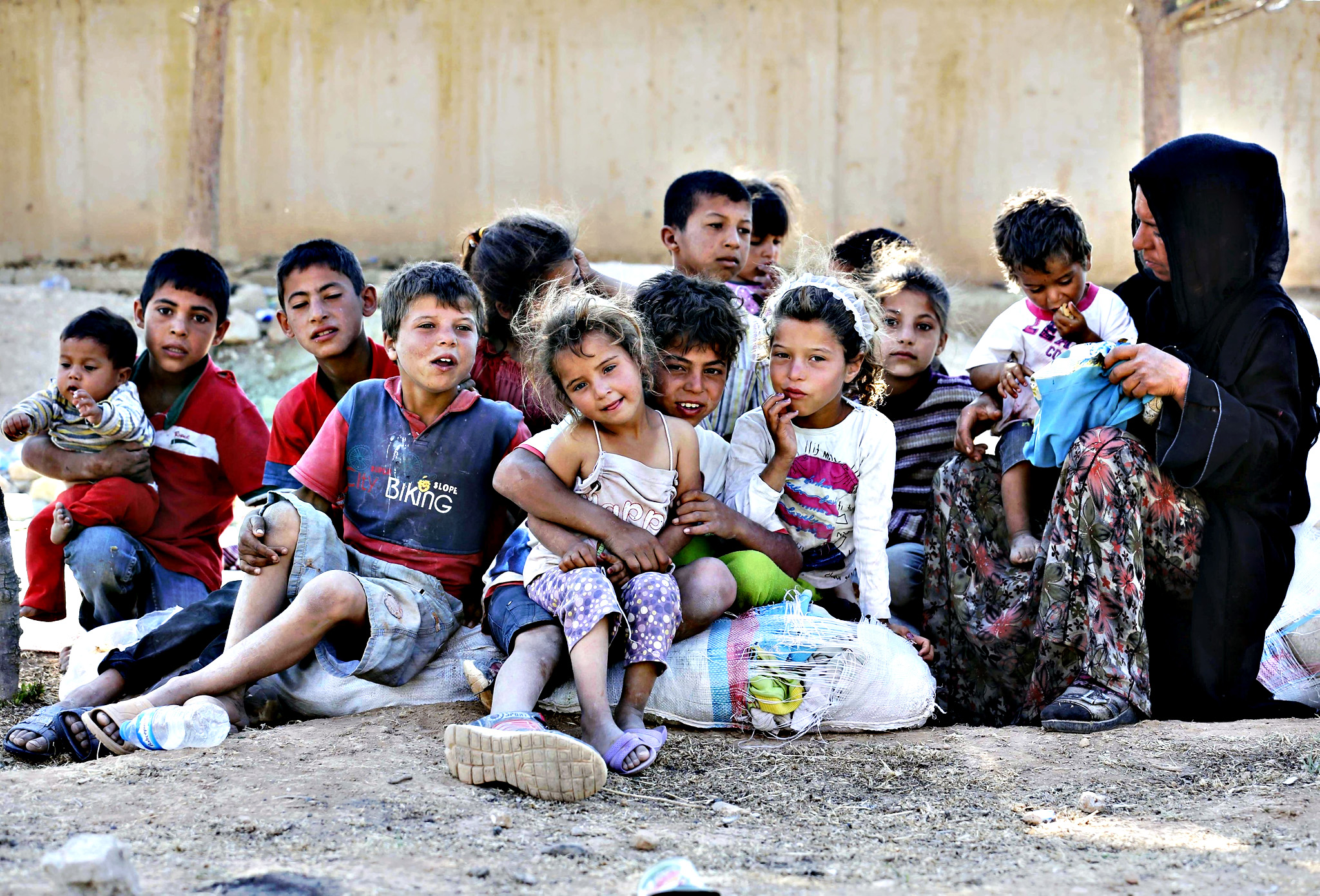 Syrian refugees take a rest at the Akcakale border gate after crossing into Turkey in Sanliurfa province, June 15, 2015. On Sunday, Turkish authorities reopened the border after a few days of closure, a security source said, adding that they expected as many as 10,000 people to come across.