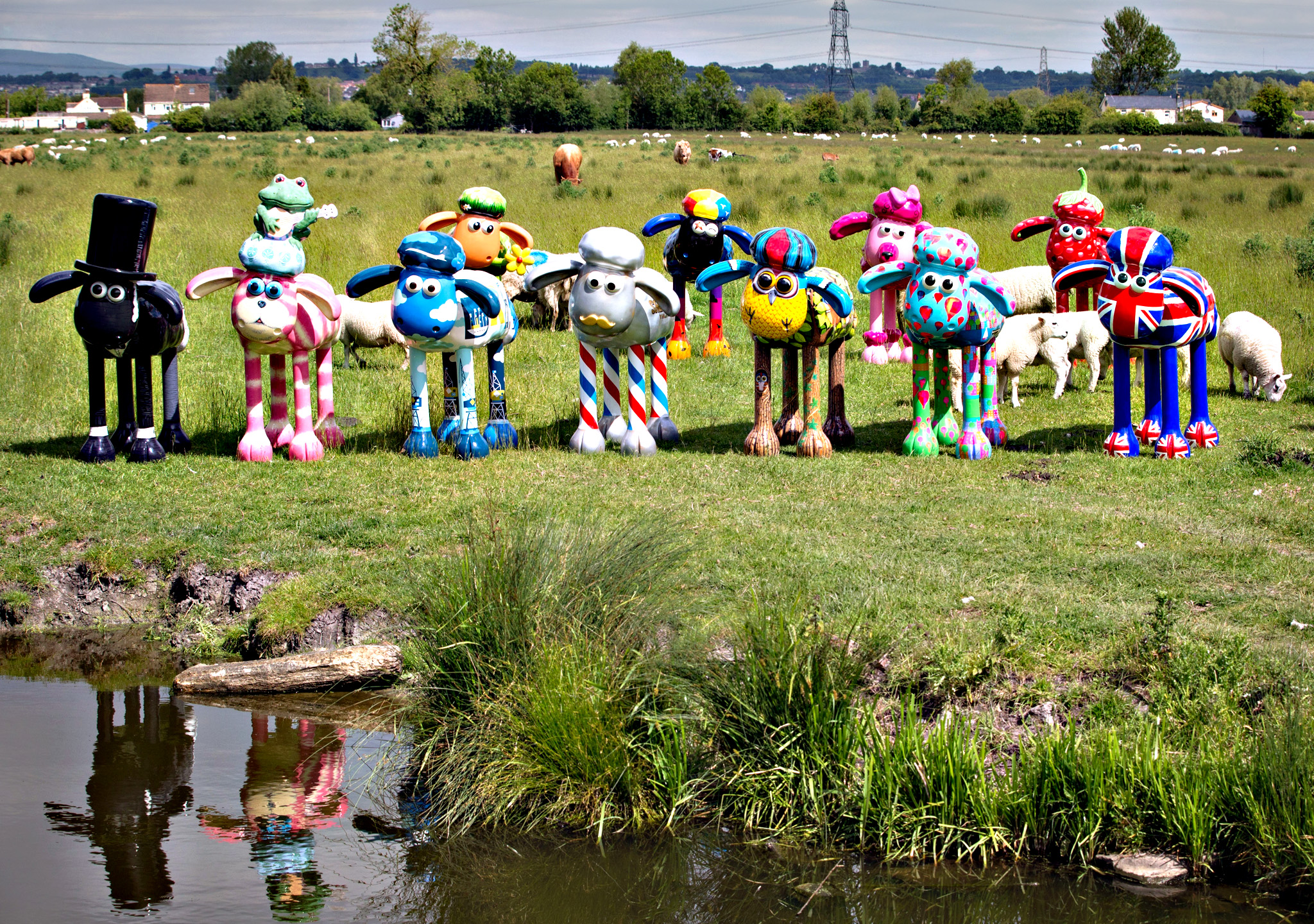 Sheep in a field graze close to some of the Shaun the Sheep sculptures ahead of their delivery to Bristol on a farm near Goldcliff on Wednesday in Newport, Wales. From July 6 to August 31 the children's charity is bringing 70 Shaun the Sheep sculptures to green spaces across Bristol and later in the year the flock will go to auction with funds raised going to The Grand Appeal, the Bristol's children's hospital charity