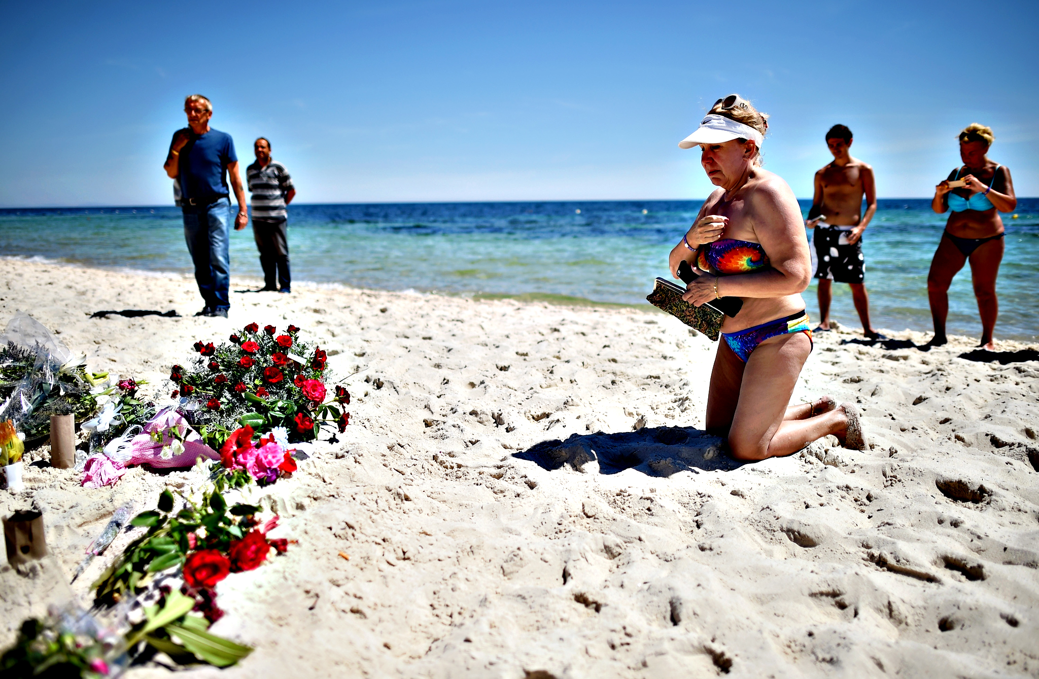 Holidaymakers react as people lay flowers on Marhaba beach, where 38 people were killed in a terrorist attack last Friday, on June 30, 2015 in Sousse, Tunisia. British police have been deployed to the area as part of one of the biggest counter terror operations since the London bombings on July 7, 2005
