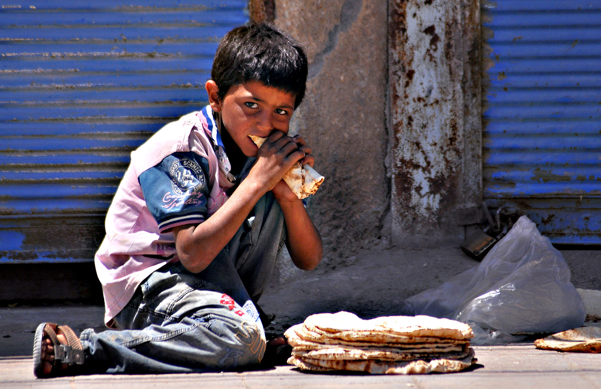 A Syrian boy eats bread as he sits on a street in the town of Tal Abyad, on the border with Turkey, on Friday, some ten days after the Kurdish People's Protection Units (YPG) seized the key transit point for Islamic State (IS) group fighters
