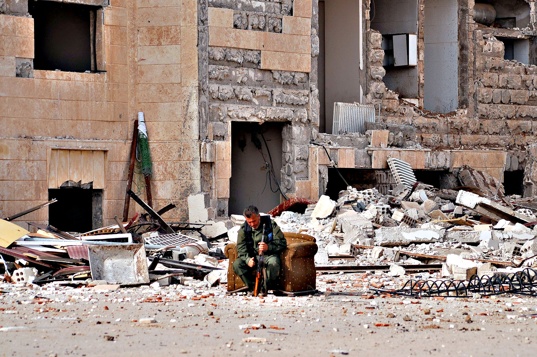 A member of the Kurdish security service sits next to the rubble of the security service headquarters in the northeastern Syrian city of Hasakeh on June 28, 2015, days after Islamic State (IS) group targeted the building with an explosive-rigged vehicle. IS seized two neighbourhoods in southern Hasakeh last week in a new attempt to seize the provincial capital, causing tens of thousands of people to flee, according to the United Nations
