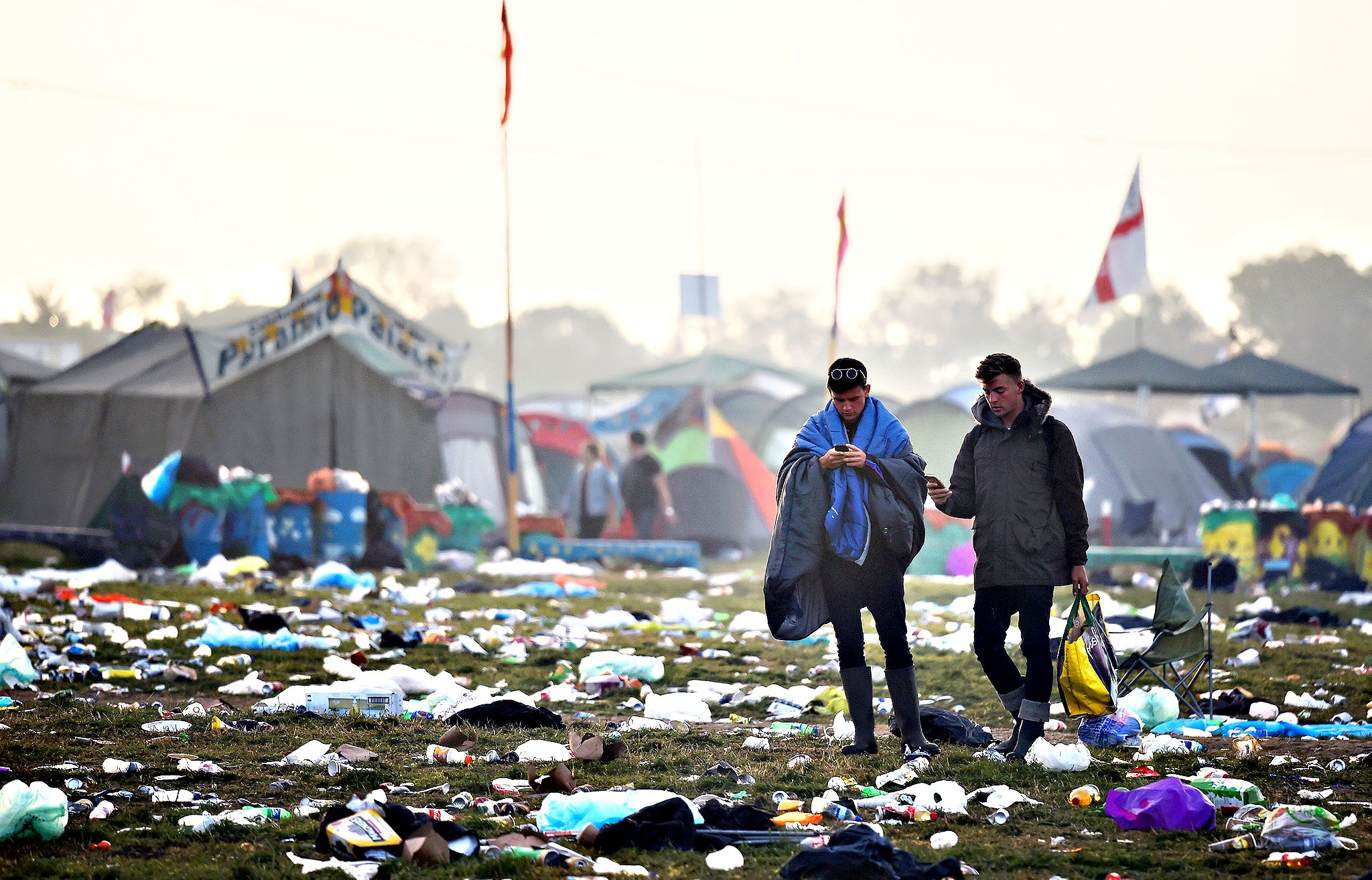 Revellers walk through rubbish left in front of the Pyramid Stage as they leave Worthy Farm in Somerset after the Glastonbury Festival in Britain June 29, 2015