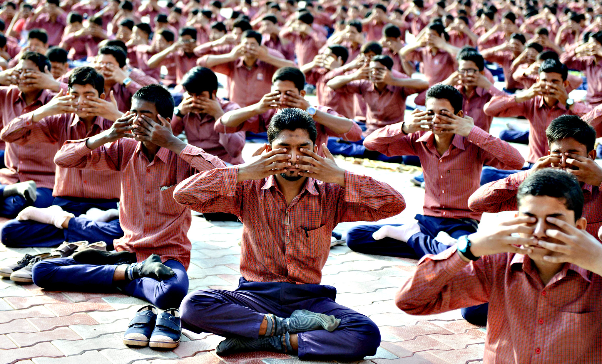 Indian school students attend a yoga workshop conducted by teachers from The Sri Sri Ravi Shankar Institute at The FD Higher Secondary School in Ahmedabad on Tuesday.  Some 1300 students situated in the Muslim dominated Juhapura area of the western Indian city participated on the first day of a five day workshop. Events will be held across the nation on June 21, to mark World Yoga Day.