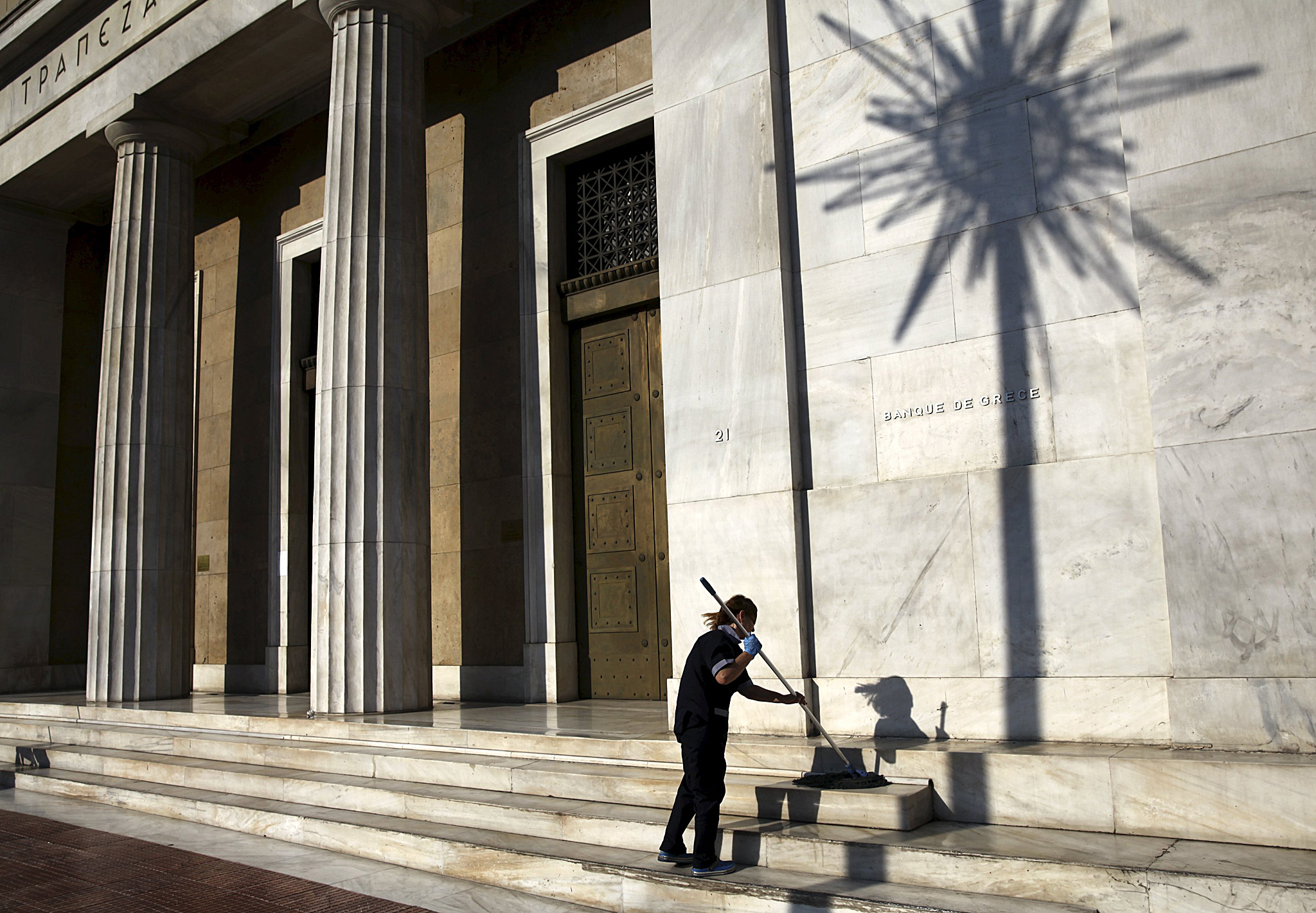 A cleaning lady mops the steps at the main entrance of the Bank of Greece headquarters in Athens...A cleaning lady mops the steps at the main entrance of the Bank of Greece headquarters in Athens, Greece  July 15, 2015. Greek banks will remain closed through to Thursday, the finance ministry said ahead of a parliamentary vote over tough austerity measures demanded by Greece's creditors in return for a third bailout.  REUTERS/Yiannis Kourtoglou