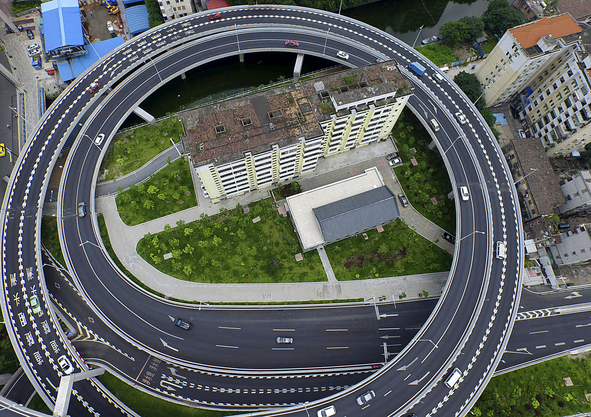 An old residential building is seen surrounded by a newly-built ring viaduct, in Guangzhou...An old residential building is seen surrounded by a newly-built ring viaduct, in Guangzhou, Guangdong province, China, June 18, 2015. The building was planned to be demolished, but several units in the building refused to move out as they couldn't reach a compensation agreement with the authority, local media reported. Picture taken June 18, 2015. REUTERS/Ma Qiang/Southern Metropolis Daily CHINA OUT. NO COMMERCIAL OR EDITORIAL SALES IN CHINA           TPX IMAGES OF THE DAY