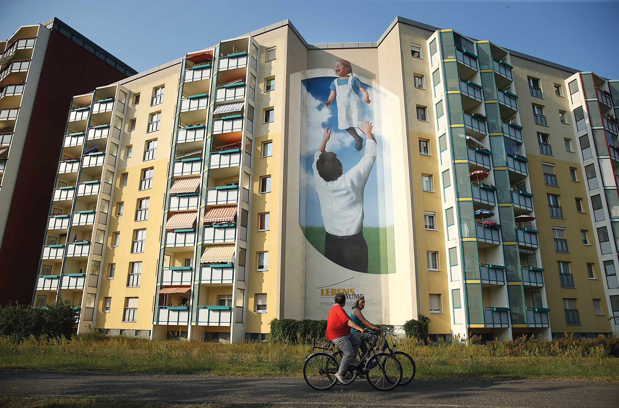 HOYERSWERDA, GERMANY - JULY 07:  A mural on the side of communist-era apartment blocks shows a father tossing his daughter into the air on July 7, 2015 in Hoyerswerda, Germany. Hoyerswerda was largely built by the communist East German authorities in the 1950s in order to house workers needed for nearby coal mines, power plants and factories, and by 1981 had a population of over 70,000. After the collapse of the communist government in 1989 the factories shut down and coal production declined, resulting in a population that has sunk to around 34,000 today, making Hoyerswerda the city with the starkest population decline in Germany. 25 years since German reunification eastern Germany is struggling with a low birth rate, rural emigration and unemployment rates higher than in western Germany.  (Photo by Sean Gallup/Getty Images)