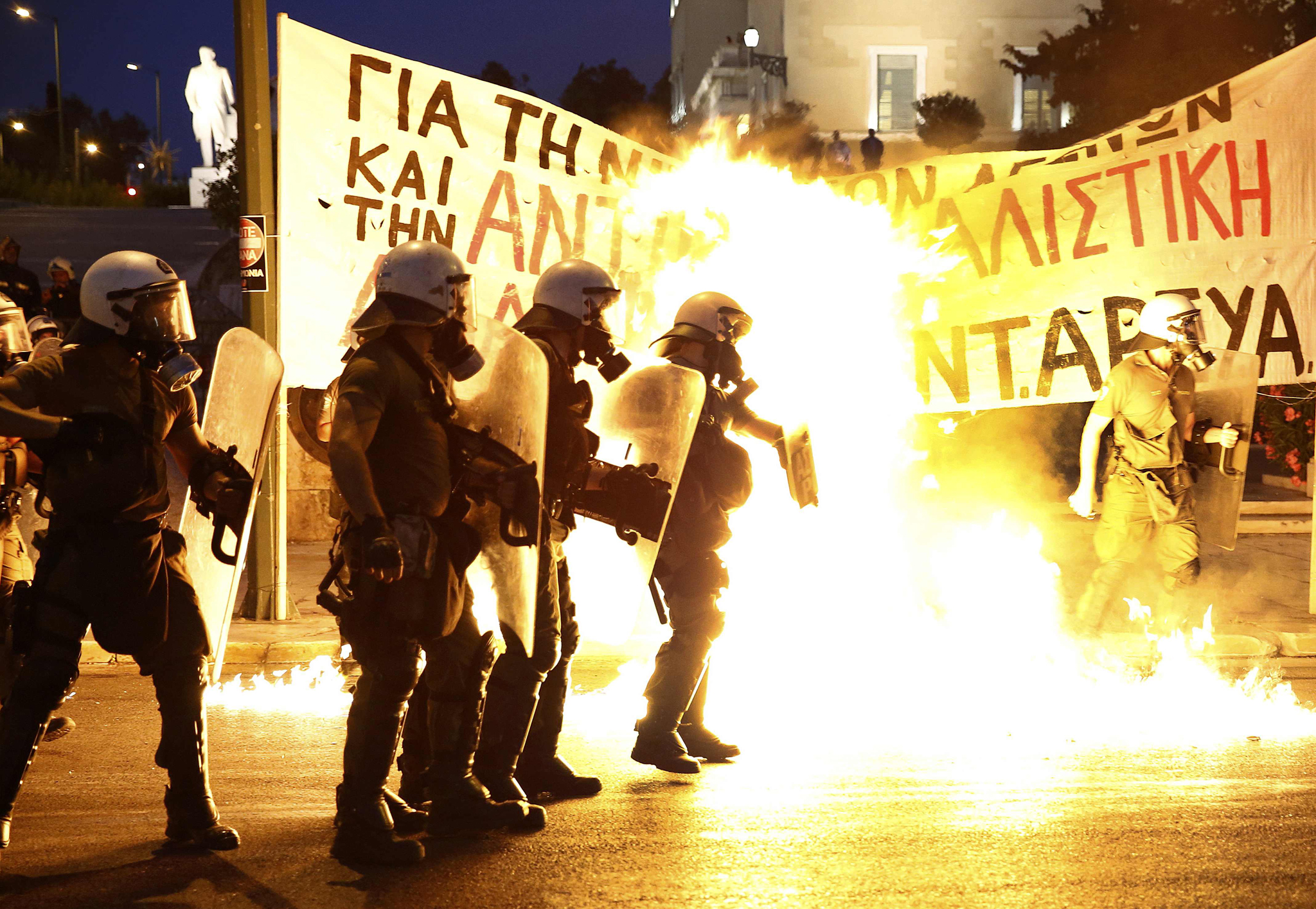 Riot police stand amongst the flames from exploded petrol bombs thrown by a small group of anti-establishment demonstrators in front of parliament in Athens, Greece July 15, 2015. Prime Minister Alexis Tsipras battled to win lawmakers' approval on Wednesday for a bailout deal to keep Greece in the euro, while the country's creditors, pressed by the IMF to provide massive debt relief, struggled to agree a financial lifeline. REUTERS/Yannis Behrakis