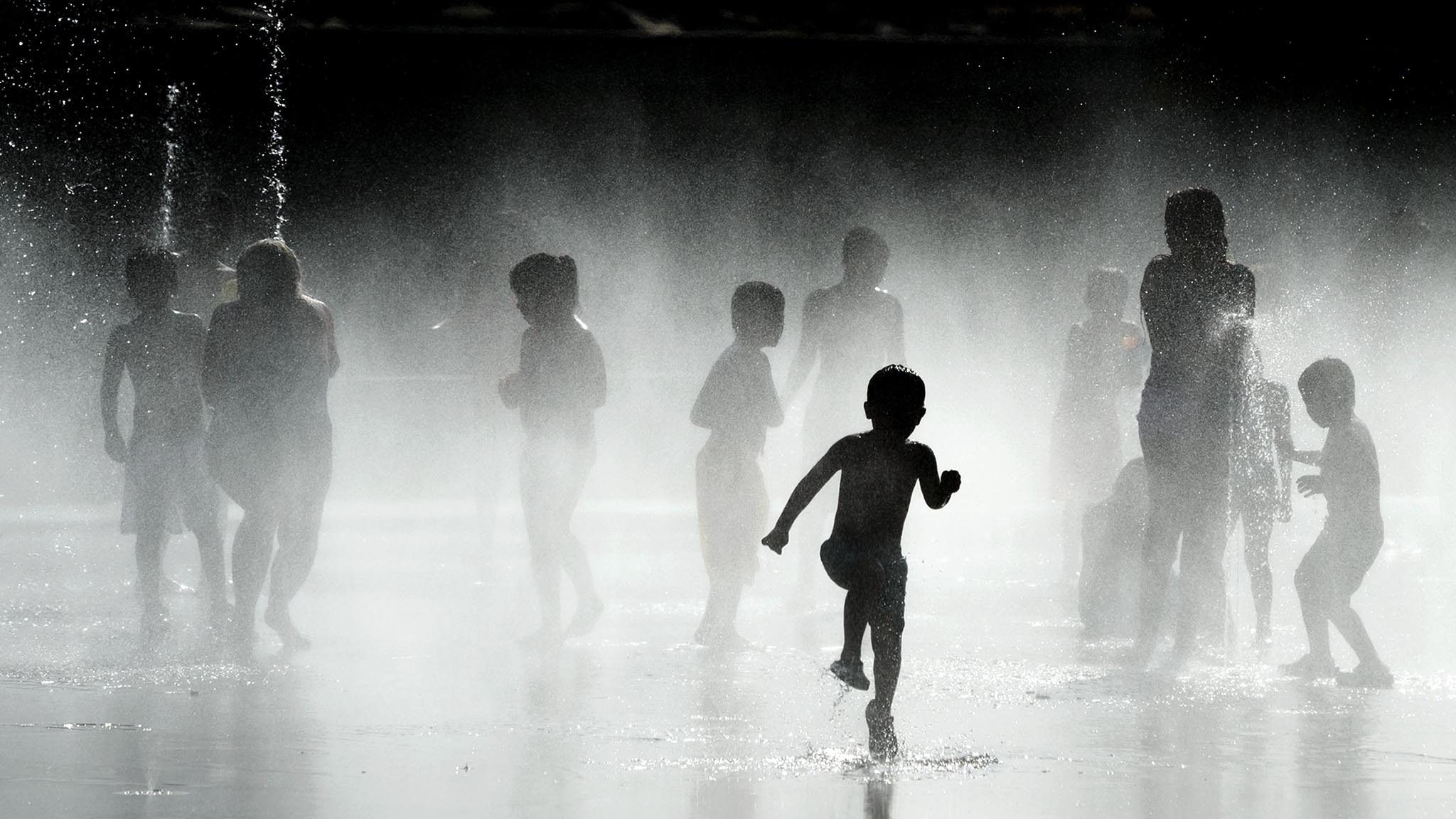 Children play with the water of fountains on the banks of the Manzanares river