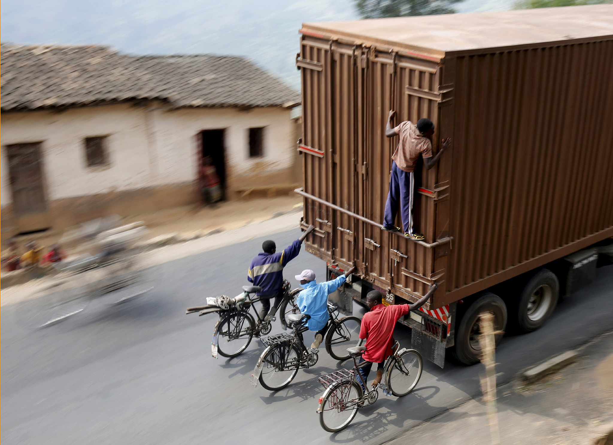 "Cylists hang to the back of a truck outside the capital Bujumbura, July 19, 2015,  as the country awaits next week's presidential elections. Each day scores of cyclists make the 45 kilometer downhill journey at breakneck speed from Bugarama to sell bananas, often hanging from the back of trucks for the return uphill trip.  REUTERS/Mike Hutchings       TPX IMAGES OF THE DAY REUTERS NEWS PICTURES HAS NOW MADE IT EASIER TO FIND THE BEST PHOTOS FROM THE MOST IMPORTANT STORIES AND TOP STANDALONES EACH DAY. Search for ""TPX"" in the IPTC Supplemental Category field or ""IMAGES OF THE DAY"" in the Caption field and you will find a selection of 80-100 of our daily Top Pictures. REUTERS NEWS PICTURES."