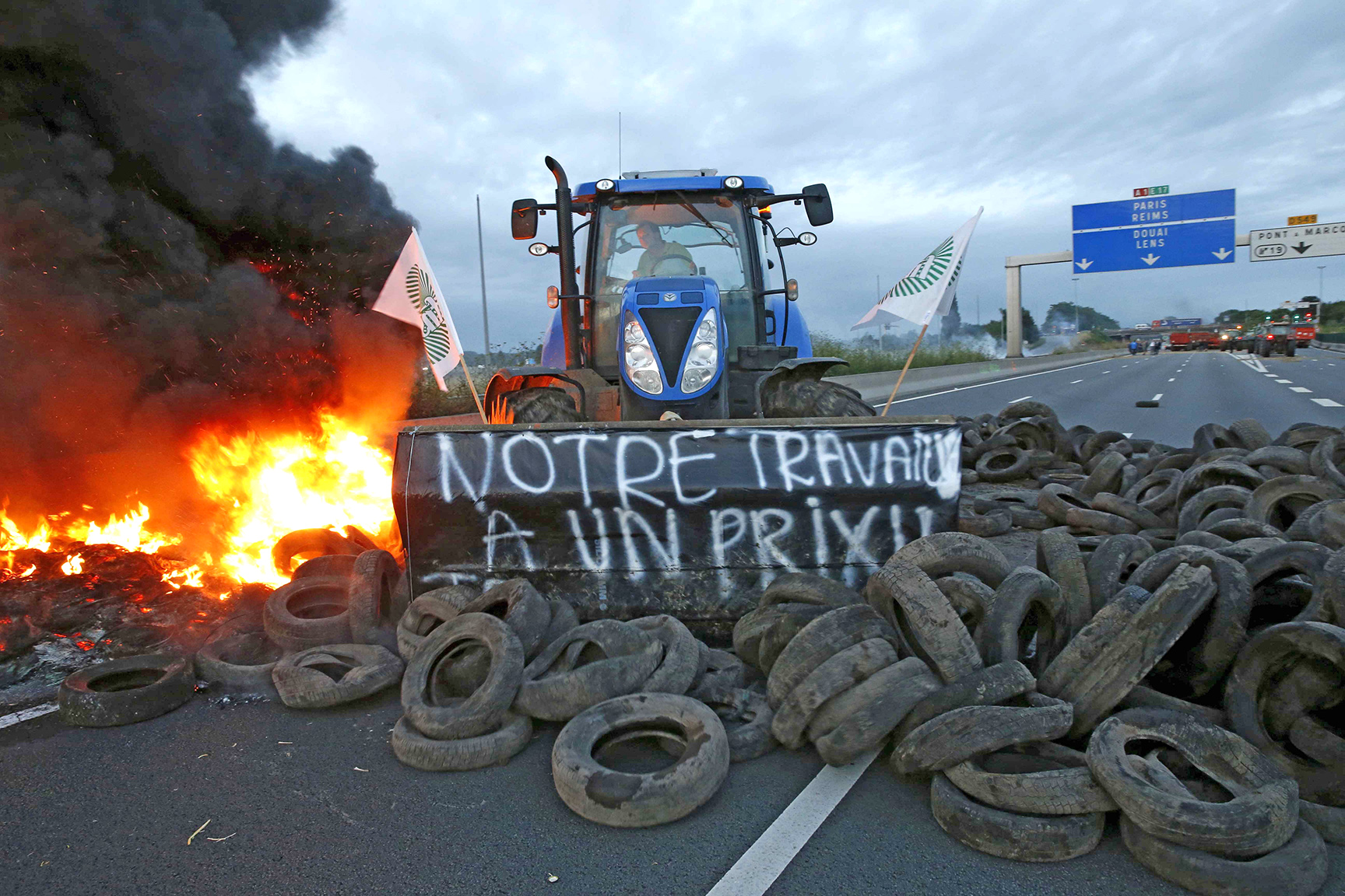A French farmer pushes tyres onto fire with his tractor to block the A1 Lille-Paris highway early in the morning in Seclin, northern France