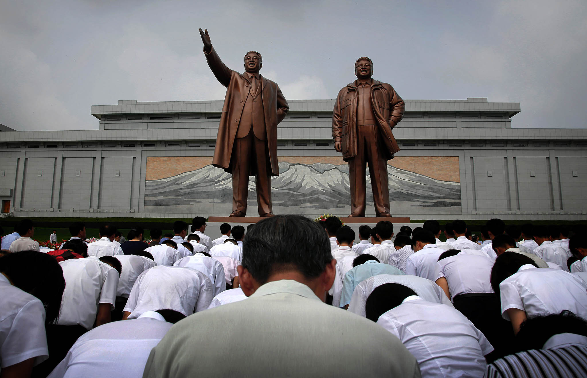 North Koreans bow in front of bronze statues of the late leaders Kim Il Sung and Kim Jong Il at Munsu Hill, Pyongyang, North Korea. North Koreans gathered to offer flowers and pay their respects to their late leaders as part of celebrations for the 62nd anniversary of the armistice that ended the Korean War.