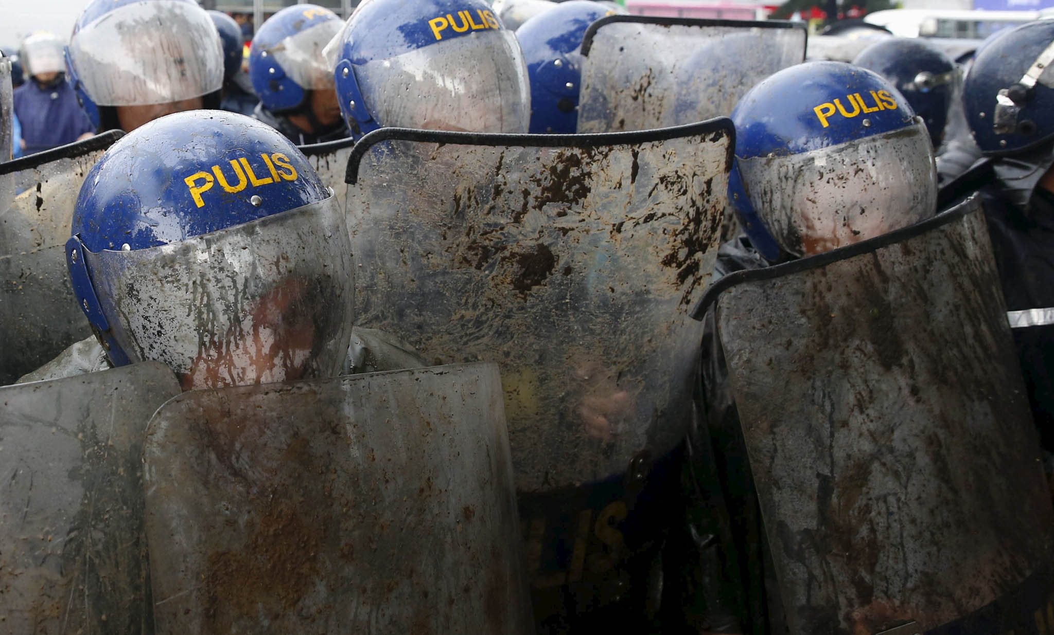 Policemen seek cover with their helmets and shields as they block protesters trying to march towards Batasang Pambansa, where Philippines President Benigno Aquino will address the joint session of Congress and deliver his last State of the Nation address in Quezon city, Metro Manila, Philippines.