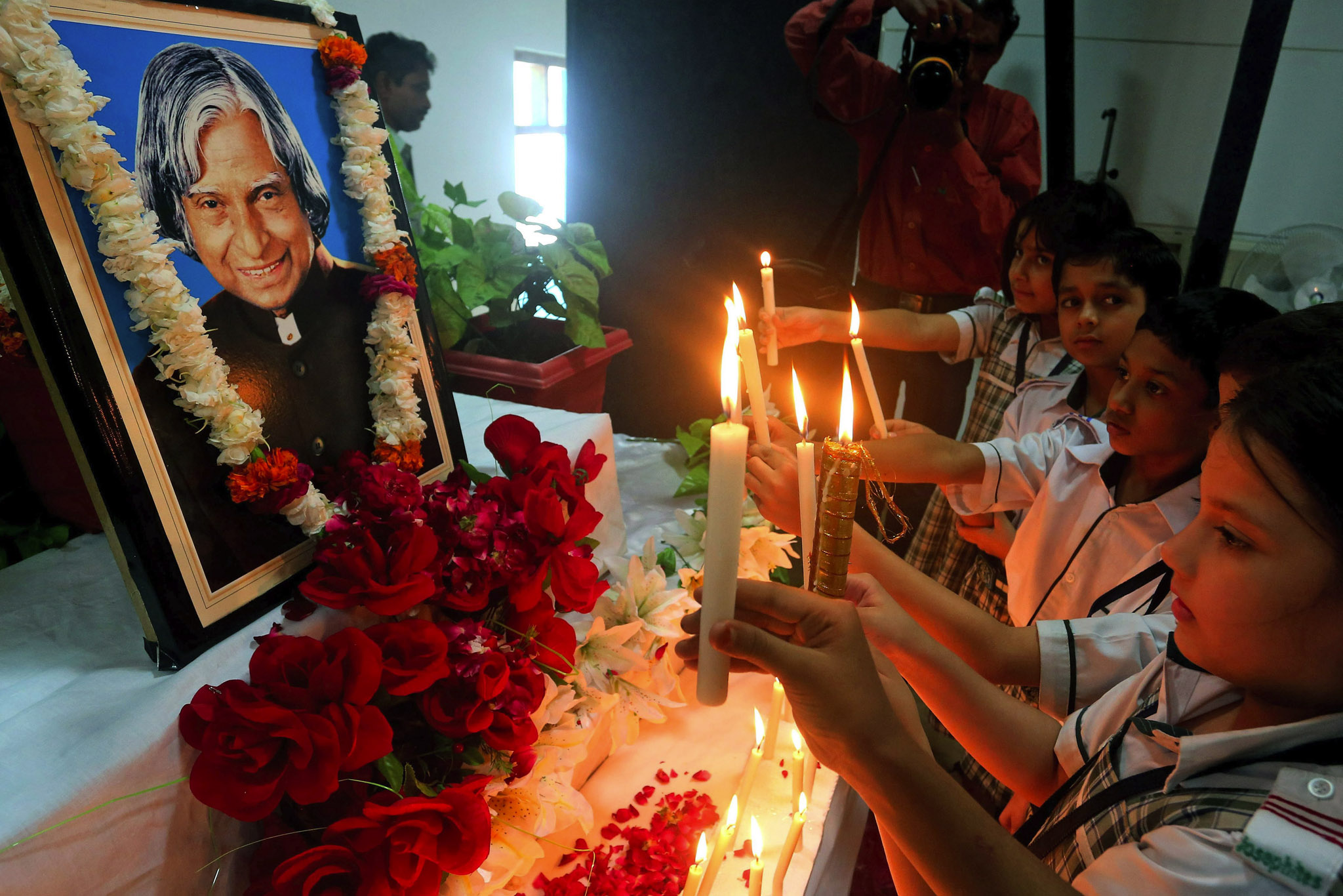 Indian school children light candles in front of a portrait of late Indian former President APJ Abdul Kalam, as they pay their respect at a school in Bhopal, India.