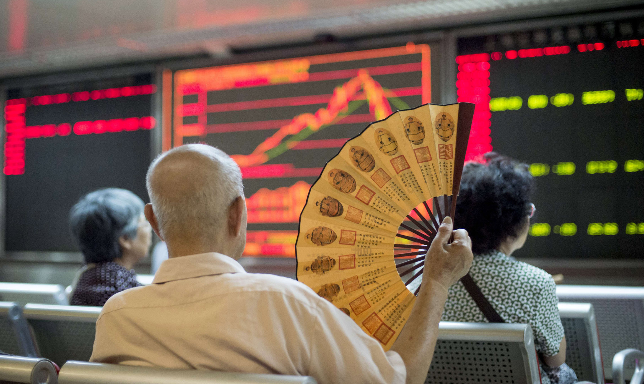 Investors look at screens showing stock market movements at a securities company in Beijing. Chinese shares sank again a day after Shanghai's steepest one-day slide in eight years, defying renewed government vows of support that analysts warned were not enough to soothe nervous investors.