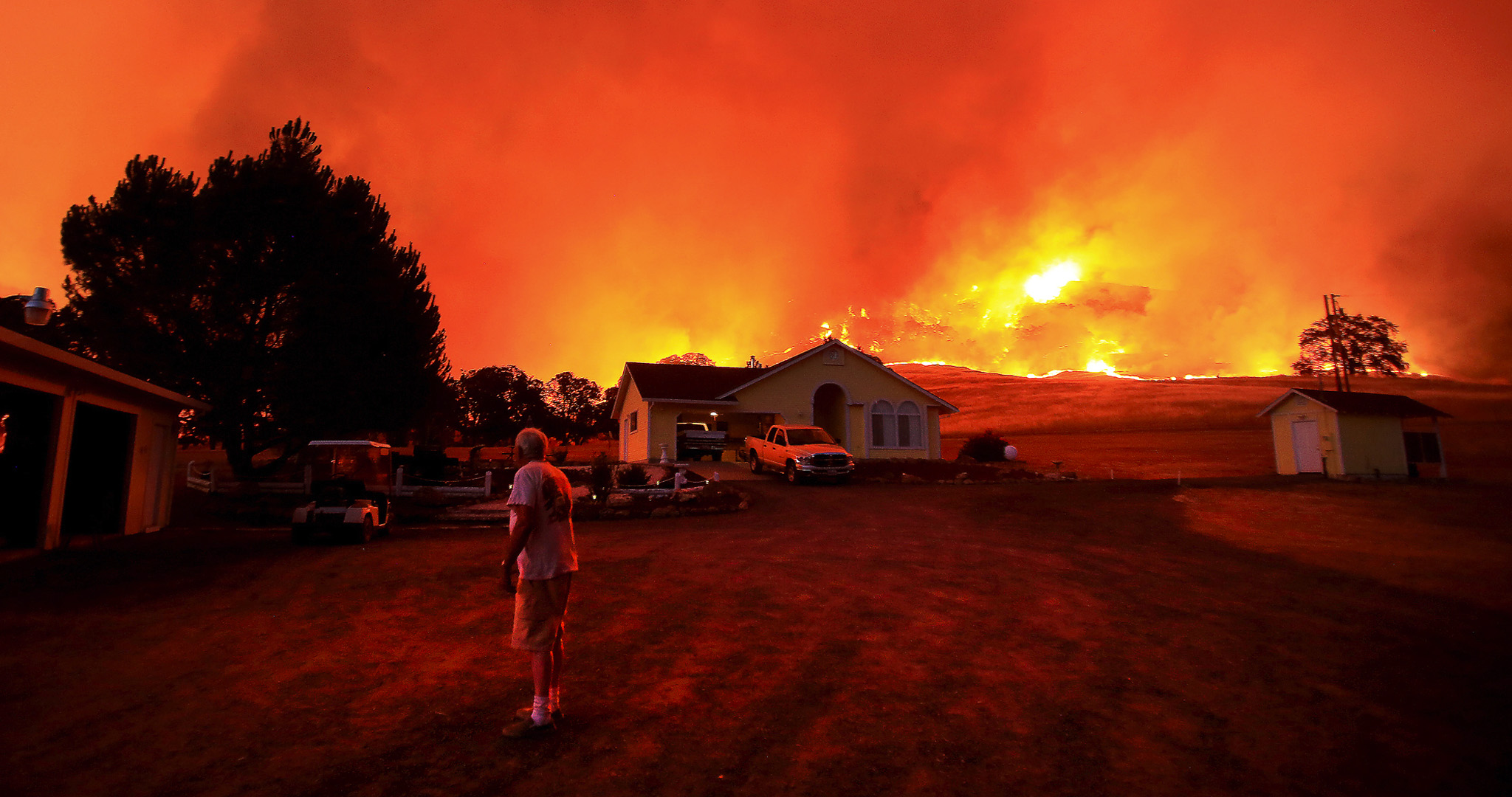A wall of flames lurches over a ridge as a resident of Morgan Valley Road near Lower Lake, California, prepares to evacuate because of the 3,000 acre Rocky Fire that has taken hold in Lake County.