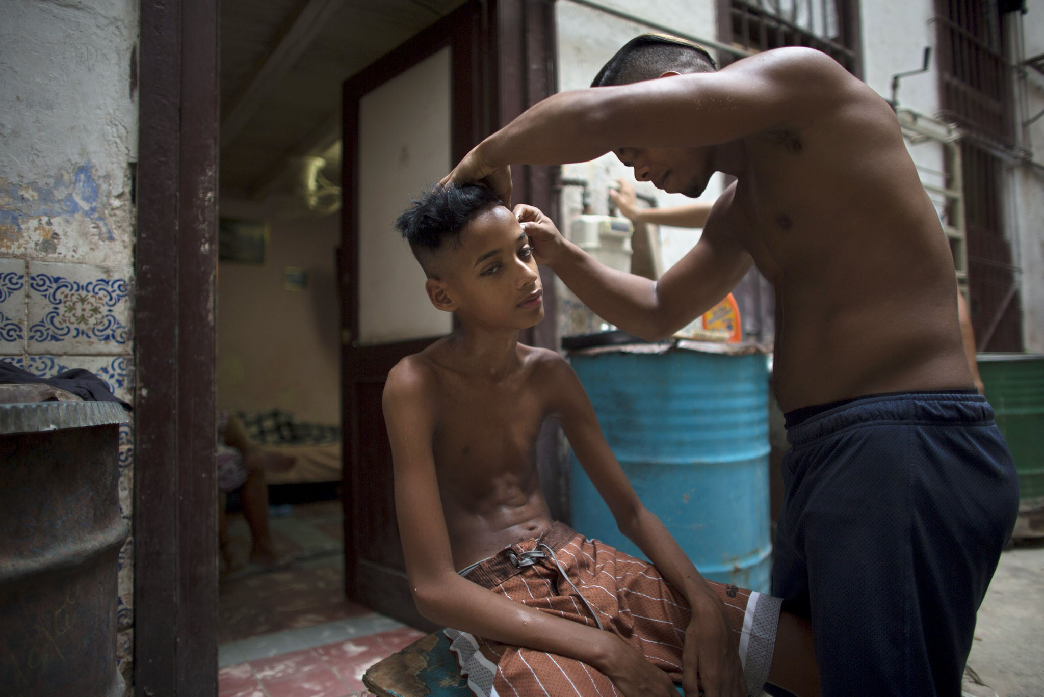 Samuel Garcia, 12, has his hair cut by a friend at the doorstep of his home in Havana, Cuba.