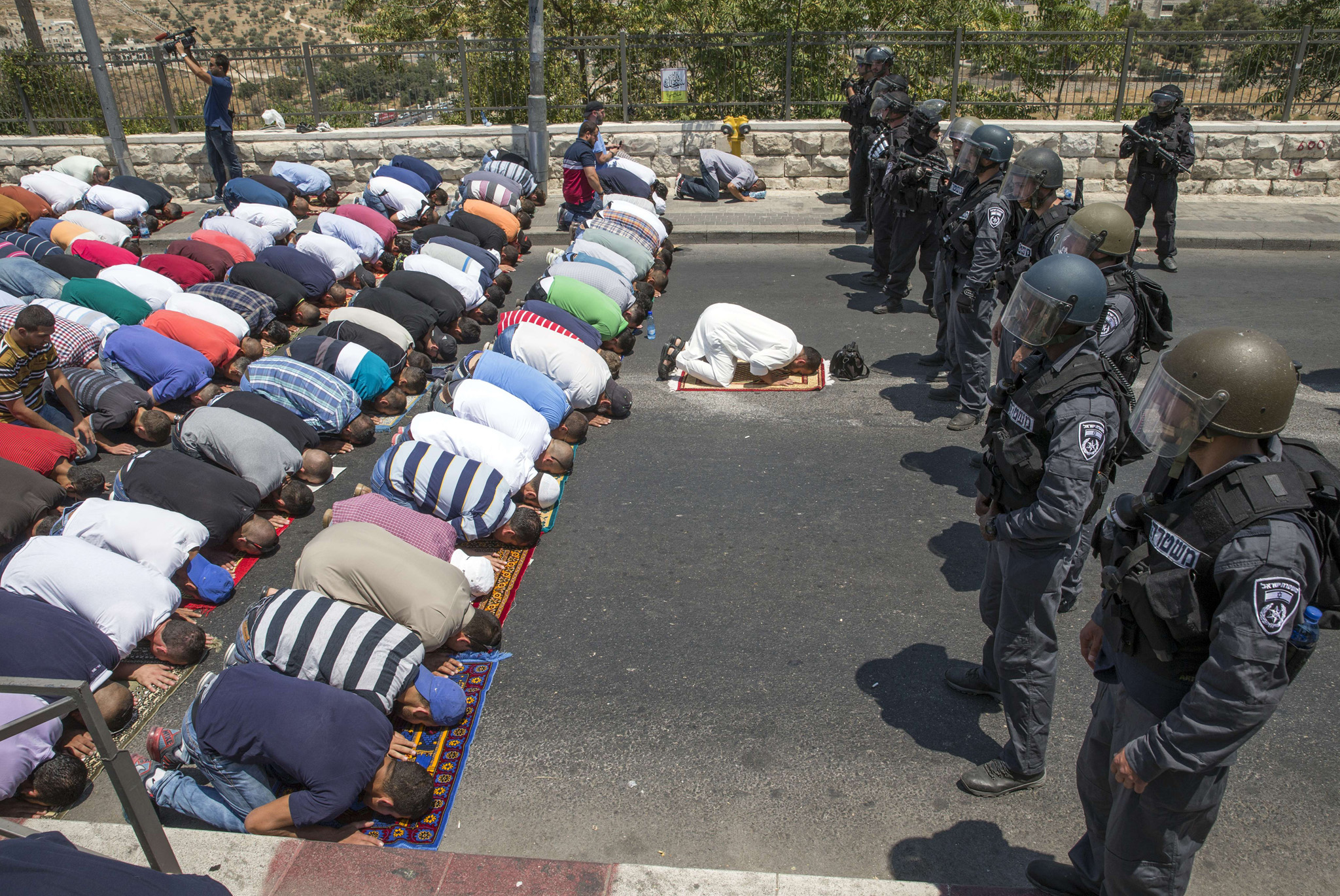 Muslim worshipers, guarded by Israeli police, pray on the streets of the Wadi al-Joz neighborhood in east Jerusalem, following restrictions by Israeli police to only allow men above 50-year-old to access the Al-Aqsa Mosque compound.
