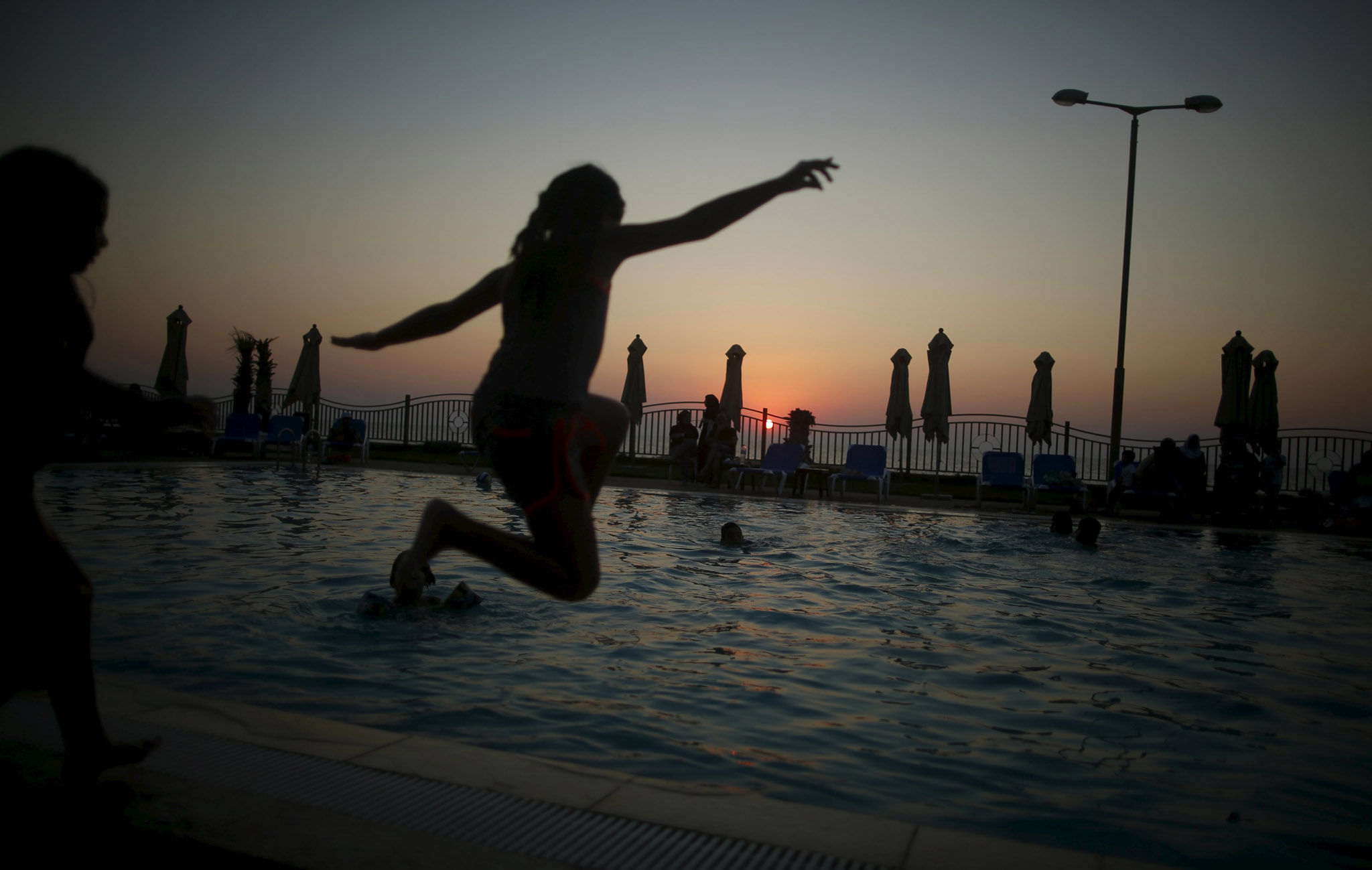 A Palestinian girl jumps into a swimming pool as she enjoys the warm weather with her family at the Blue Beach Resort in Gaza