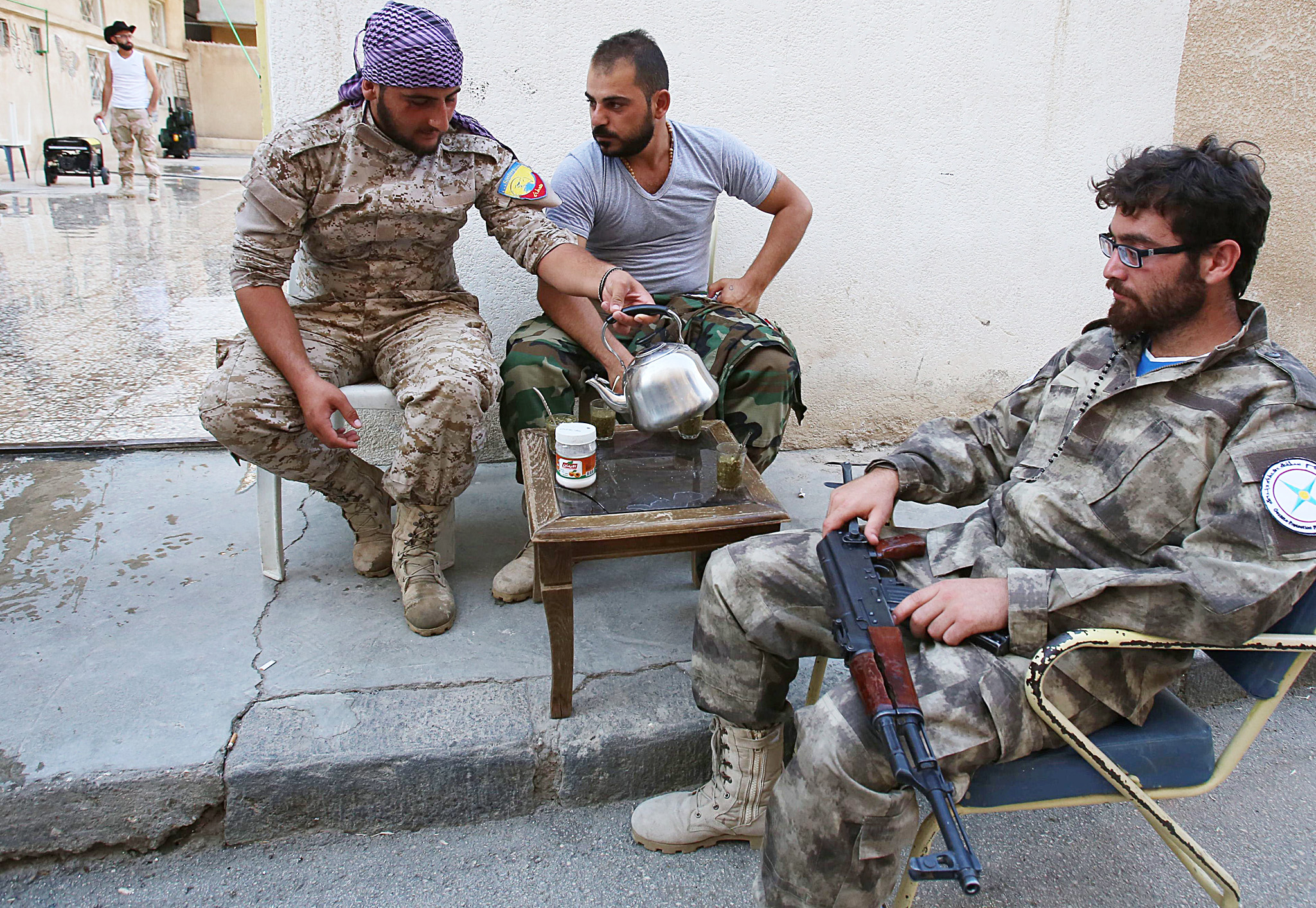 Members of the Assyrian Gozarto Protecti...Members of the Assyrian Gozarto Protection Forces (GPF), consisting of Sutoro militia, a pro-government Syriac Christian movement, and other Assyrian fighters rest and drink tea before heading to reinforce pro-government forces on the front line in the battle against the Islamic State (IS) group, in the northeastern Syrian province of Hasakeh on July 13, 2015. AFP PHOTO / YOUSSEF KARWASHANYOUSSEF KARWASHAN/AFP/Getty Images