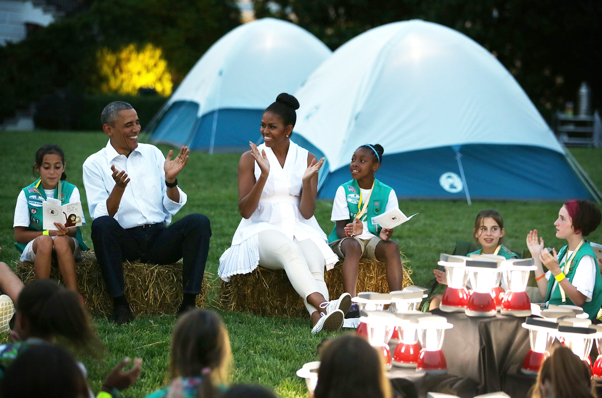 President, First Lady Host Girls Scouts At First-Ever White House Campout...WASHINGTON, DC - JUNE 30:  U.S. President Barack Obama (2nd L) and first lady Michelle Obama (3rd L) particiapte in campfire songs session with fourth-grade Girl Scouts during the first-ever White House Campout June 30, 2015 at South Lawn of the White House in Washington, DC. The first lady hosted the event, as part of her Let's Move! Outside initiative, for Girl Scouts to participate in activities to earn their Camper Badge, and to celebrate the release of the new Girls' Choice Outdoor badges.  (Photo by Alex Wong/Getty Images)