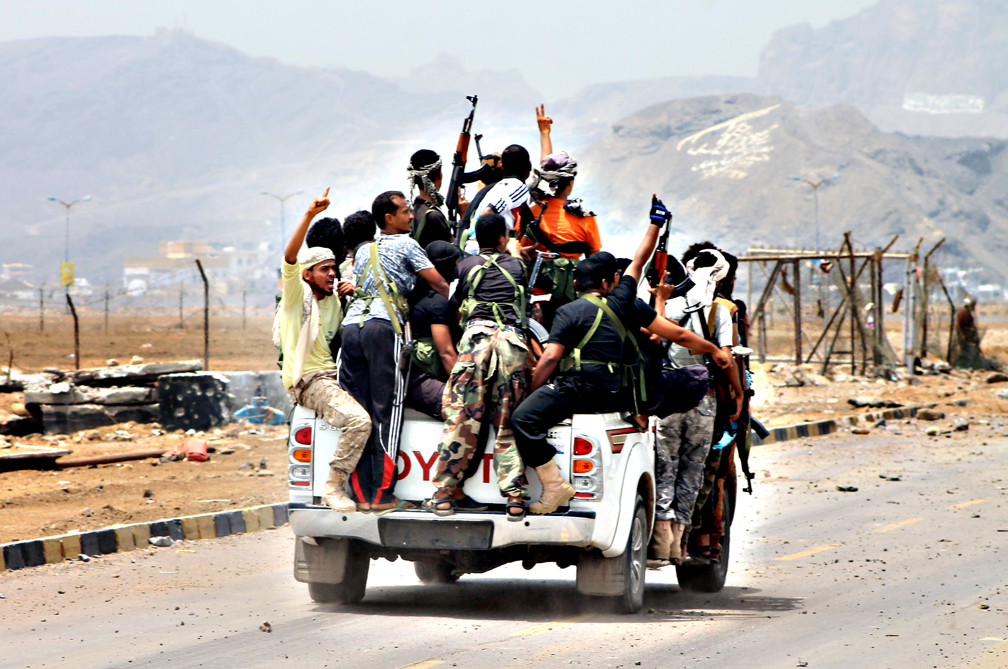 Armed militiamen loyal to Yemen's fugitive President Abderabbo Mansour Hadi drive in a pick-up truck in the Khor Maskar neighbourhood of the southern Yemeni city of Aden on July 14, 2015 near Aden's airport which they recaptured from Shiite Huthi rebels. Loyalists of Yemen's exiled president recaptured the airport in second city sealing a four-month battle with Iran-backed rebels with Saudi-led air and naval support, military sources said