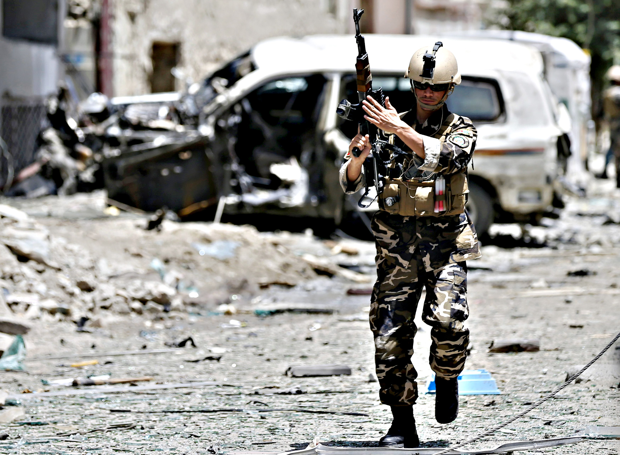 A member of the Afghan security forces keeps watch at the site of a suicide attack in Kabul, Afghanistan July 7, 2015. A suicide car bomber slammed into a convoy of foreign forces in the Afghan capital on Tuesday, the Ministry of Interior spokesman said, but it was not clear whether there were any casualties