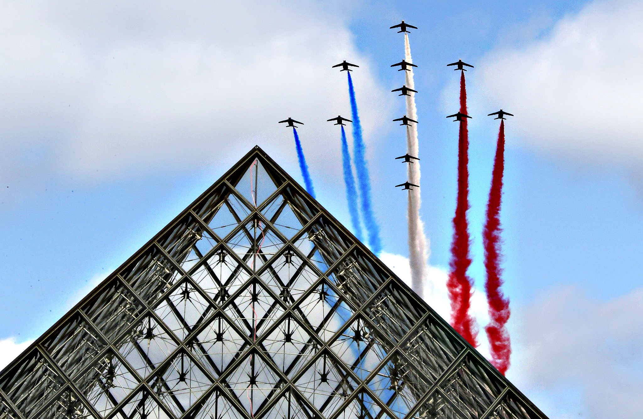 Alphajets from the French Air Force Patrouille de France fly over the Pyramid of the Louvre Museum during the traditional Bastille day military parade in Paris...Alphajets from the French Air Force Patrouille de France in the formation of a Croix de Lorraine cross and releasing trails of red, white and blue smoke, colors of French national flag, fly over the Pyramid of the Louvre Museum during the traditional Bastille day military parade in Paris, France, July 14, 2015