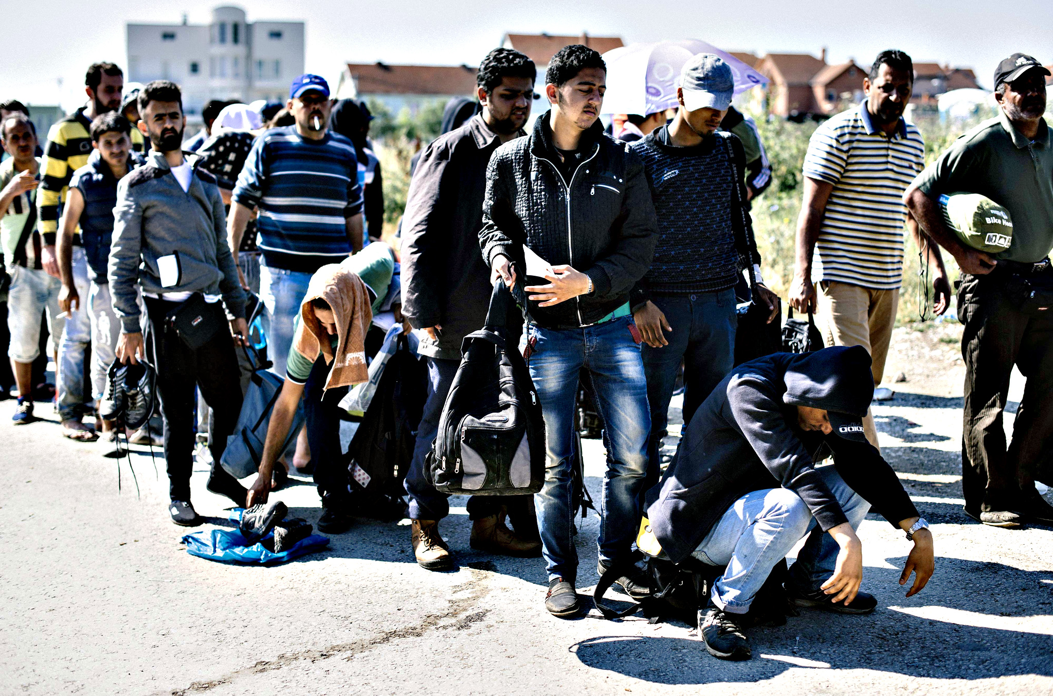Migrants stand in a queue near the police station in the southern Serbian town of Presevo, near the border with Macedonia, on Thursday. Illegal immigrants cross Serbia on their way to other European countries as it has land access to three members of the 28-nation bloc -- Romania, Hungary and Croatia. This year, more than 50,000 migrants tried to cross into Hungary via Serbia between January 1 and May 31 -- representing an 880-percent increase compared to the same period in 2014, according to the EU's Frontex border agency