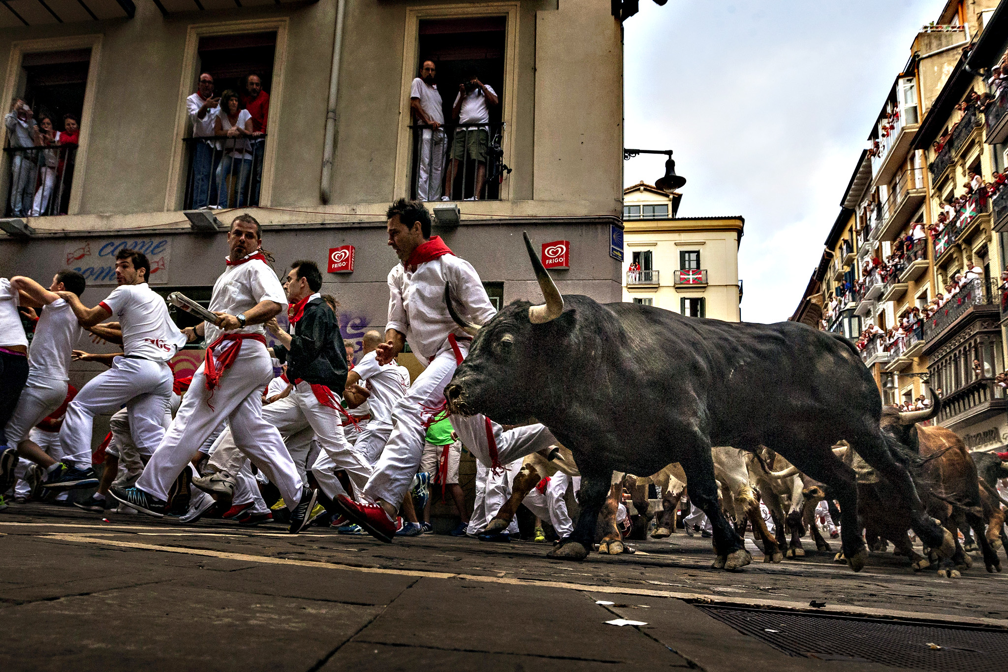 Revelers run chased by 'El Tajo y La Reina' ranch fighting bulls as they turn Estafeta corner during a running of the bulls of the San Fermin festival in Pamplona, Spain, Wednesday, July 8, 2015. Revelers from around the world arrive in Pamplona every year to take part on some of the eight days of the running of the bulls