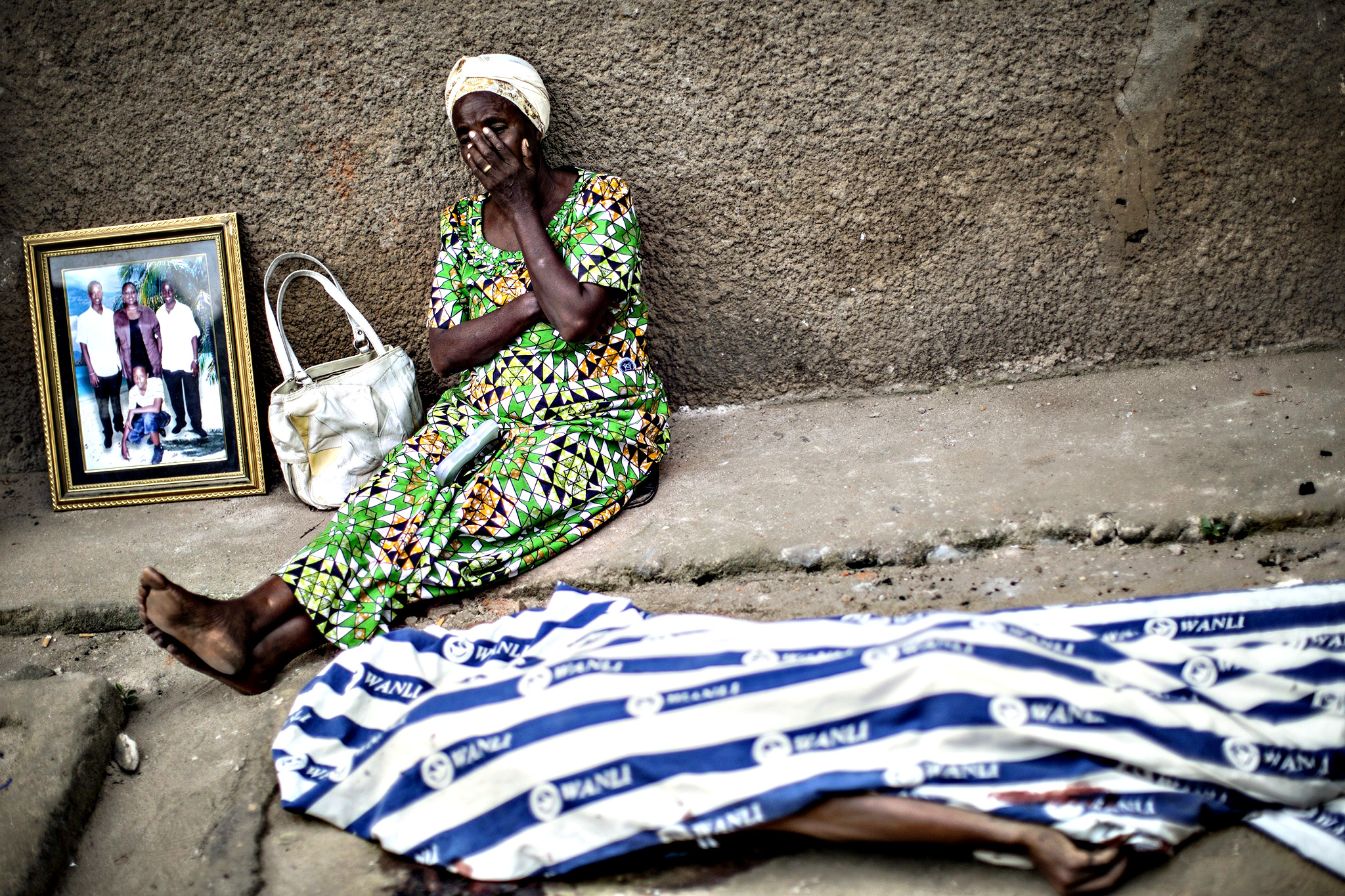 A relative sits on the floor as she grieves on Thursday next to a family portrait and the body of one of the victims of the unrest that rocked the neighbourhood of Mutakura in Bujumbura the day before, where at least six people were killed during clashes with police