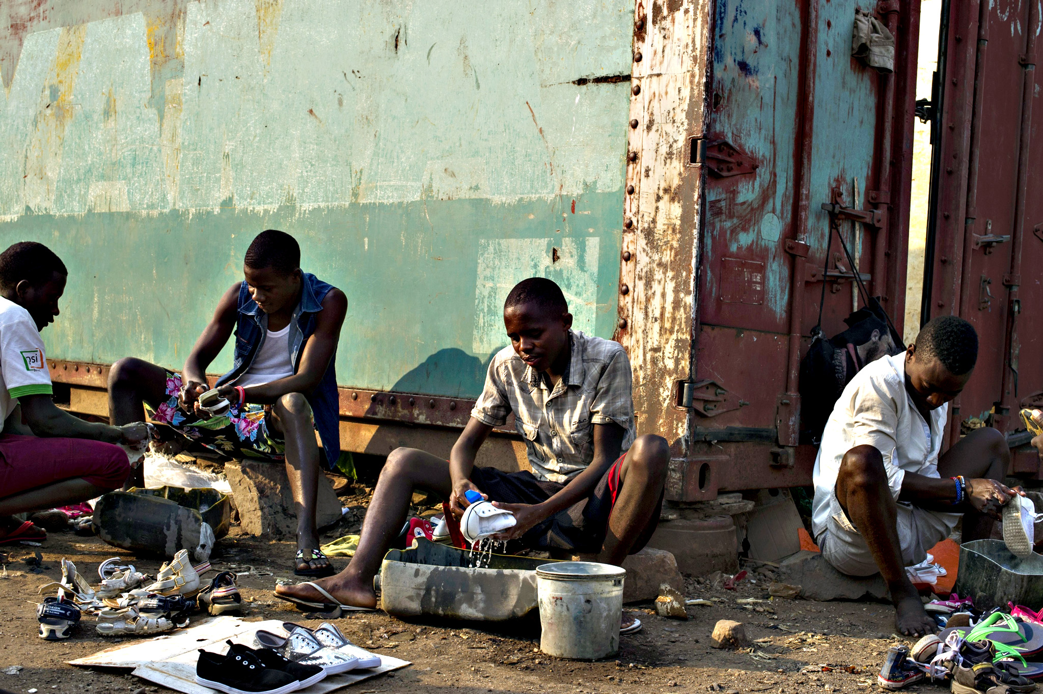 Young men clean second-hand shoes to sell them on a market in Bujumbura on July 24, 2015. Burundian President Pierre Nkurunziza is set to win a controversial third term in office, but analysts say his victory will be hollow, with the country divided, isolated and facing aid cuts