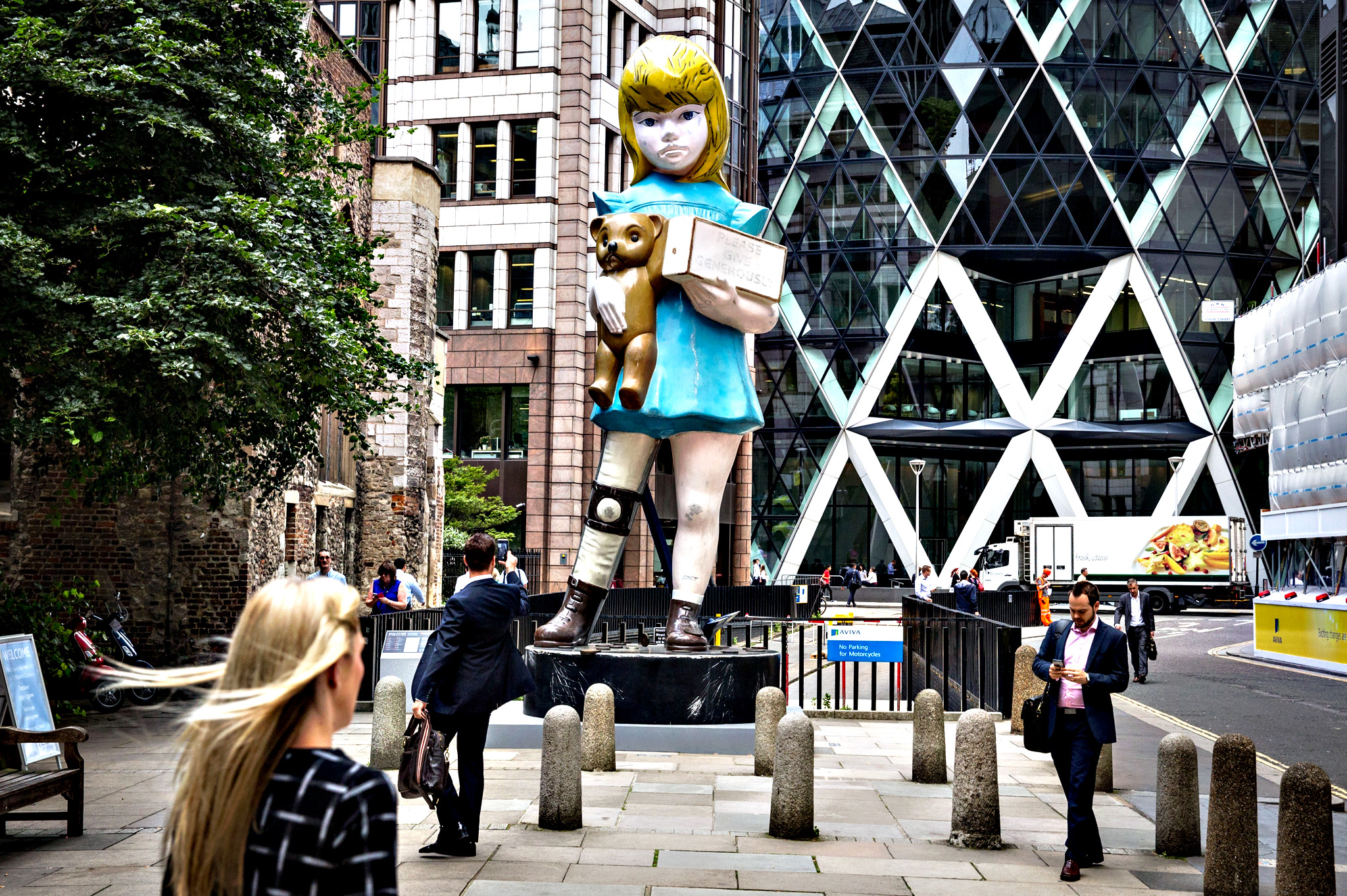 City workers walk past Damien Hirst's sculpture 'Charity' opposite the Gherkin building on July 16, 2015 in London, England.  'Charity' is a 22-foot bronze sculpture based on 1960s collection boxes for the charity Scope. The sculpture is of a young disabled girl holding a teddy bear and a request to 'Please Give Generously' whilst her back has been opened with a crow bar with the donated coins falling at her feet
