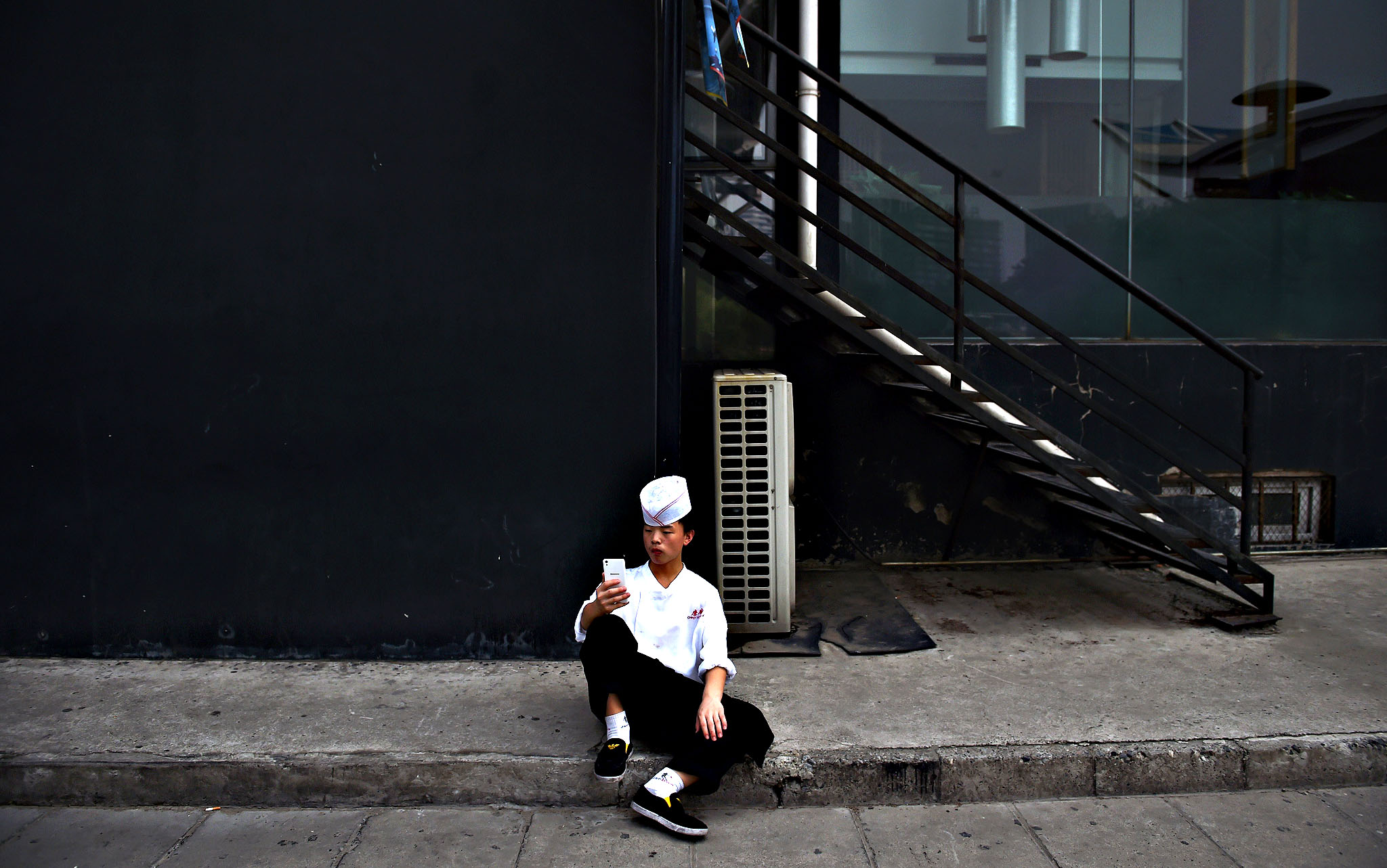 A cook uses his smartphone during a break outside a restaurant in Beijing on July 10, 2015
